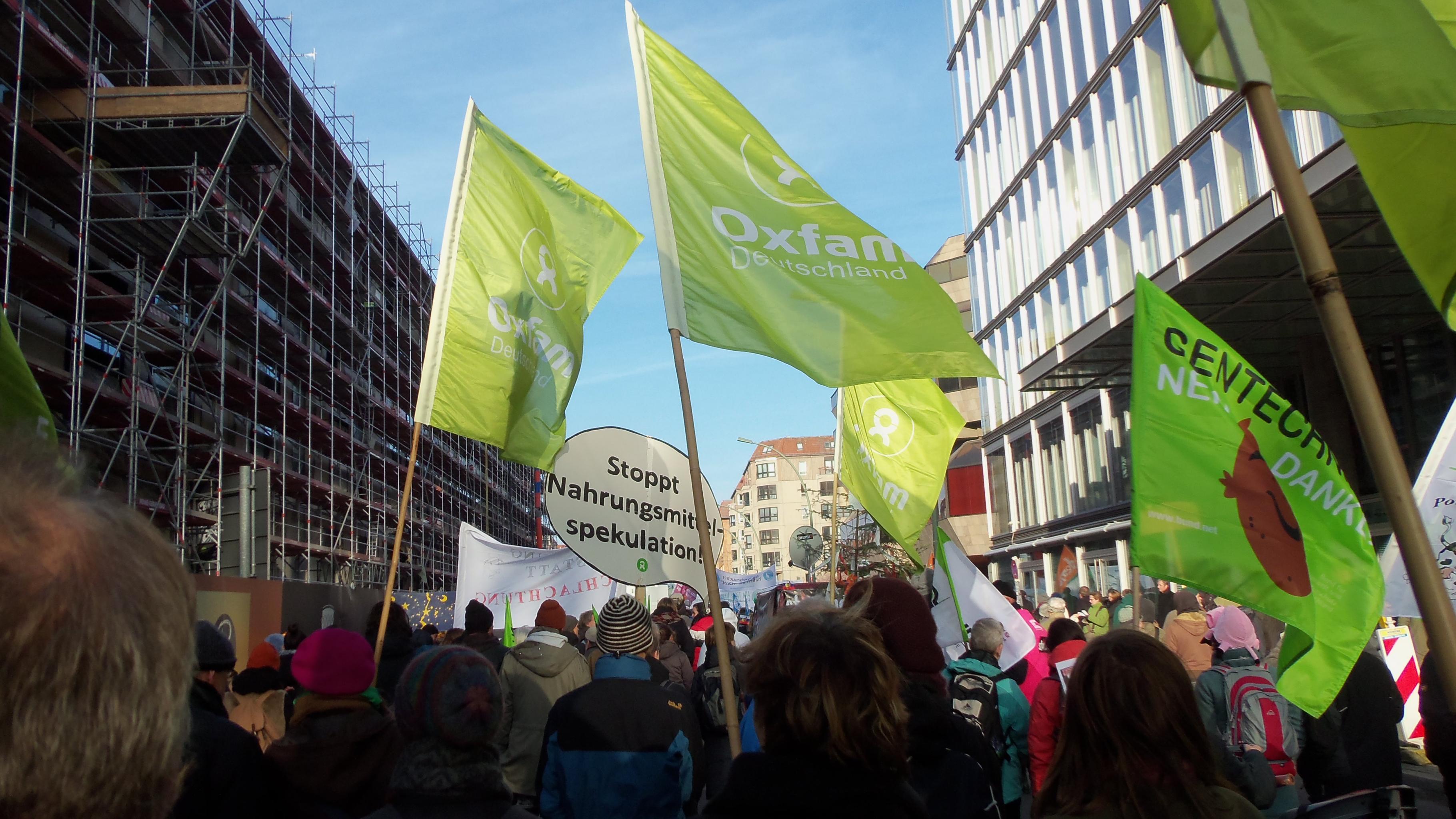 Demonstranten mit Oxfam-Fahnen auf den Straßen Berlins