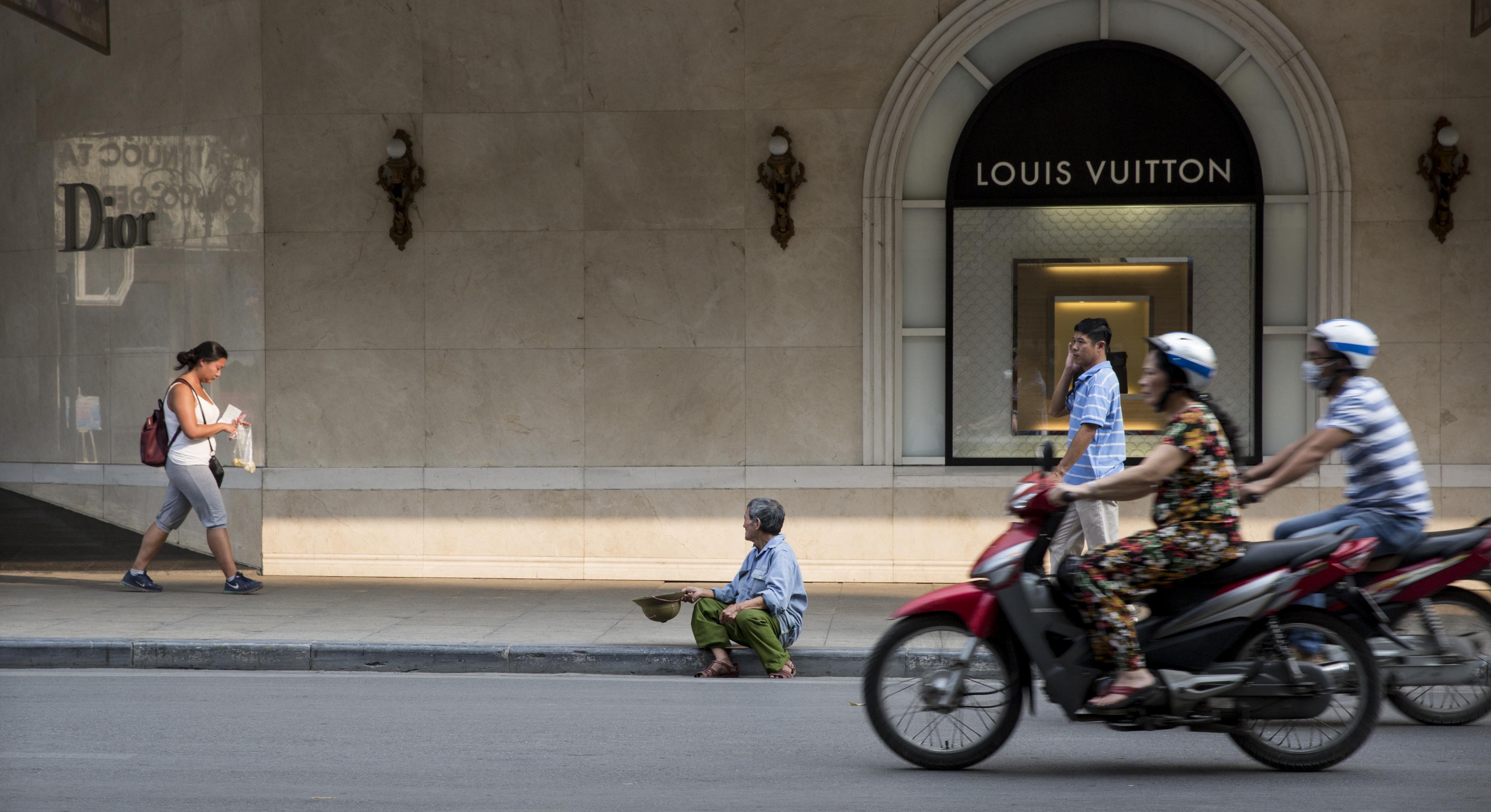 Mann sitzt vor Louis-Vuitton-Laden in Hanoi und bettelt