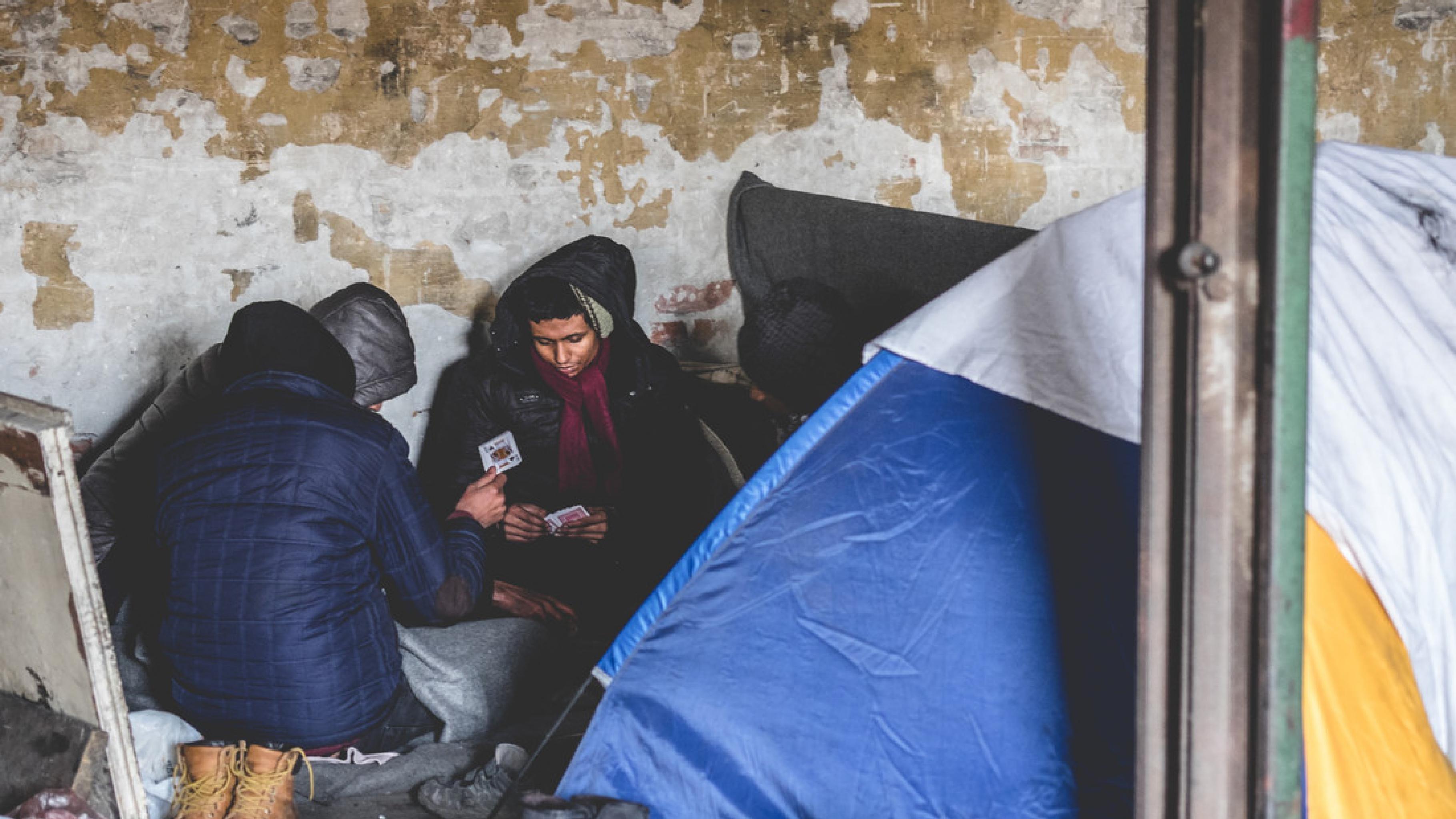 Bericht Balkan-Route: Menschen auf der Flucht spielen Karten in unzumutbaren Unterkünften