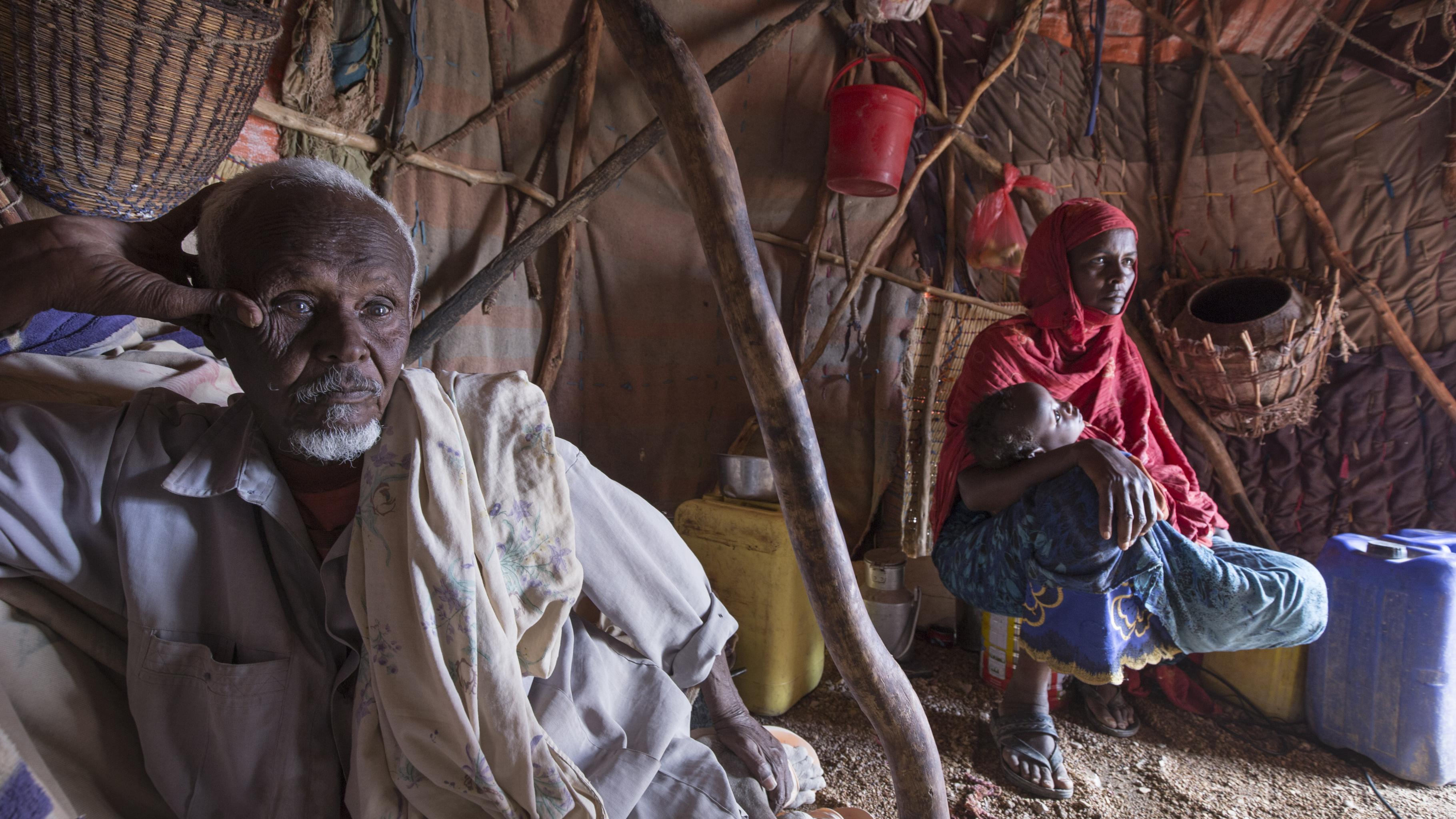 Hungerkrise Ostafrika: Ein alter Mann sitzt in einem nordüftig errichtetem Zelt.  mit einem Babay im Arm.