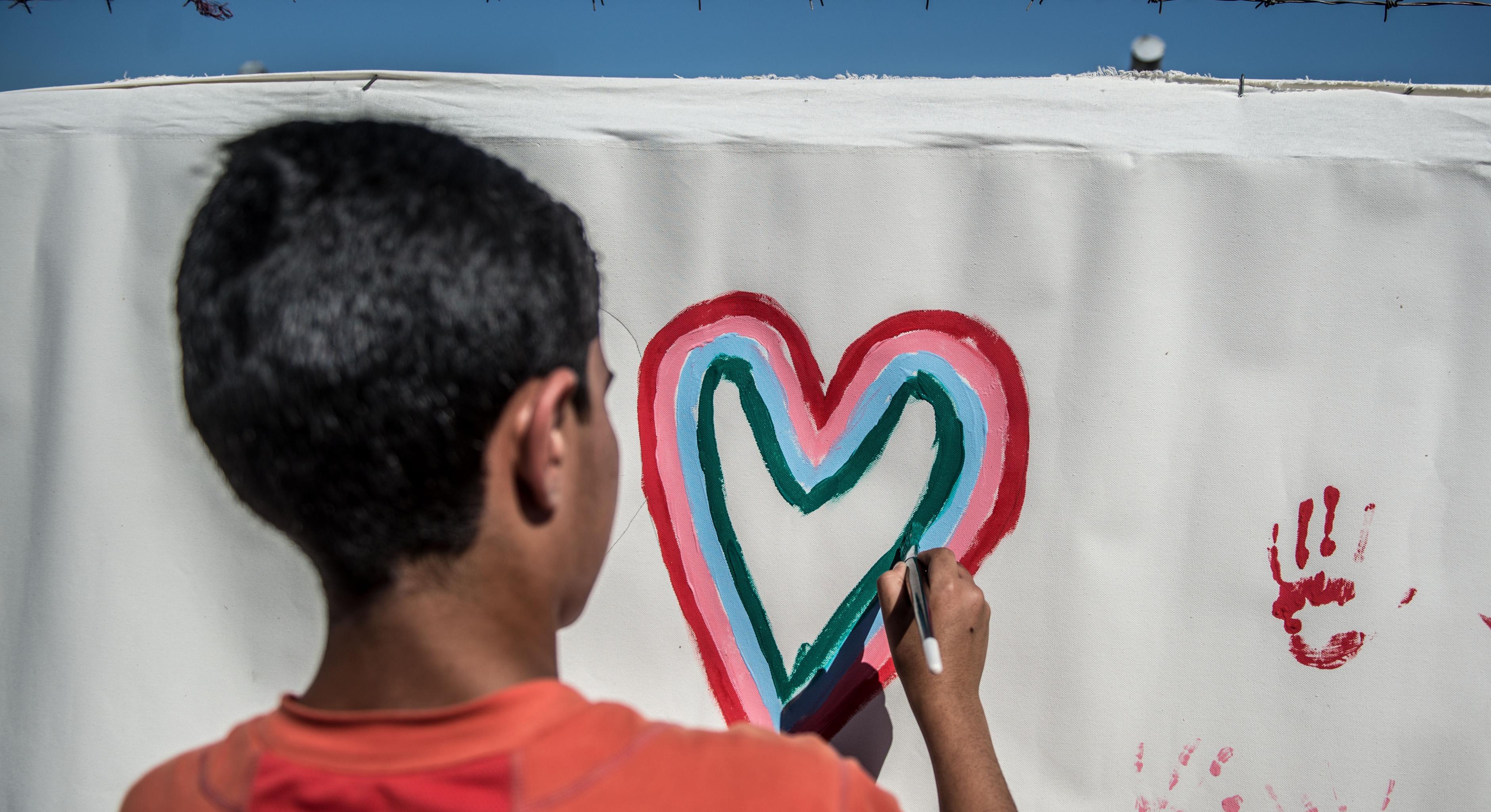 Ein irakischer Junge malt ein Herz auf eine Leinwand