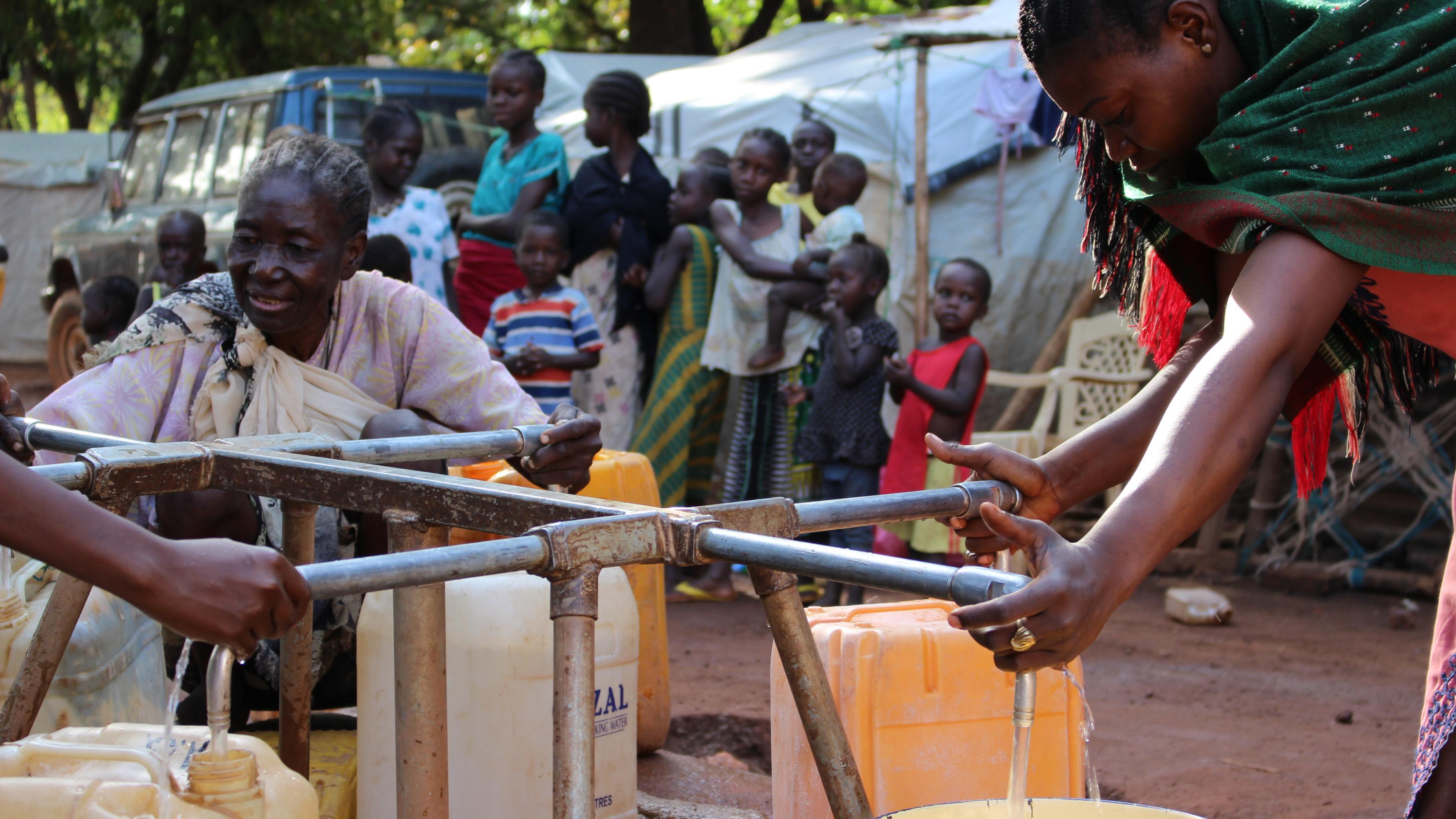 Bewohner des Lagers in Wau sammeln Wasser.