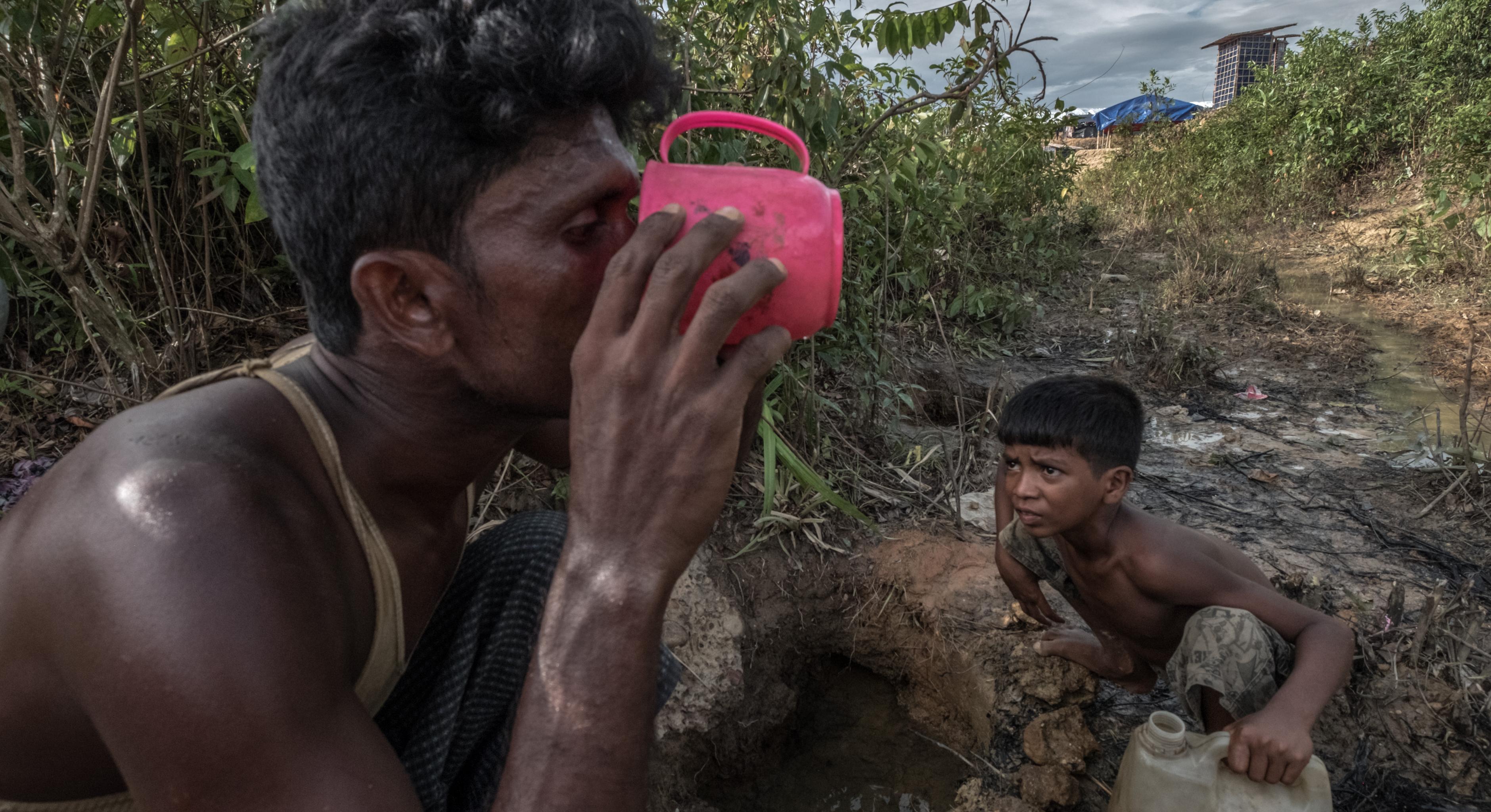 Ein Mann und ein Junge trinken Wasser aus einem schmutzigen Wasserloch in Bangladesch