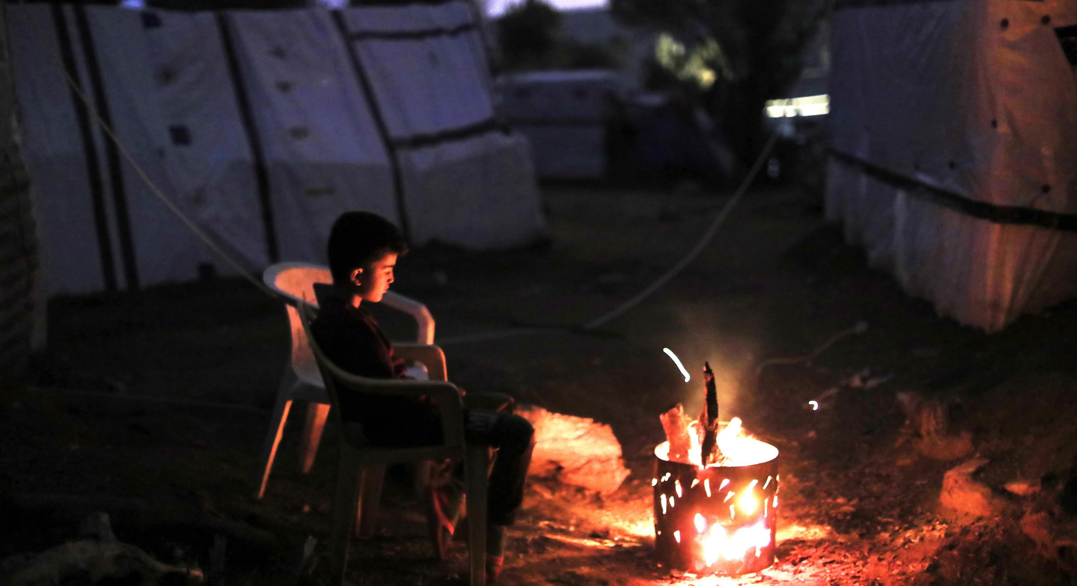 Ein Junge sitzt in einem Flüchtlingscamp vor einem kleinen Feuer