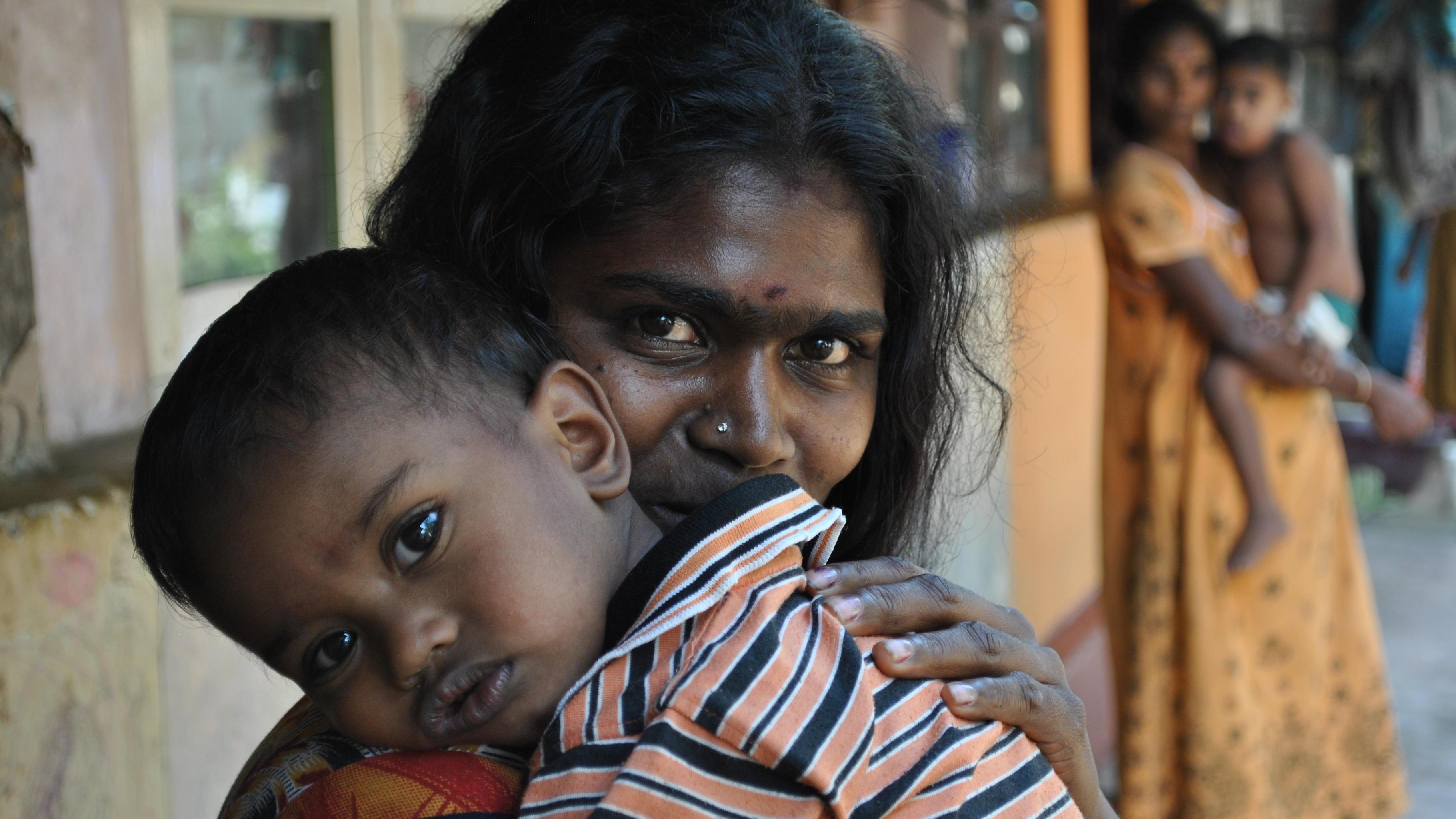 Eine Mutter mit ihrem Kind vor ihrem Zimmer in der Imboolpitiya-Plantage