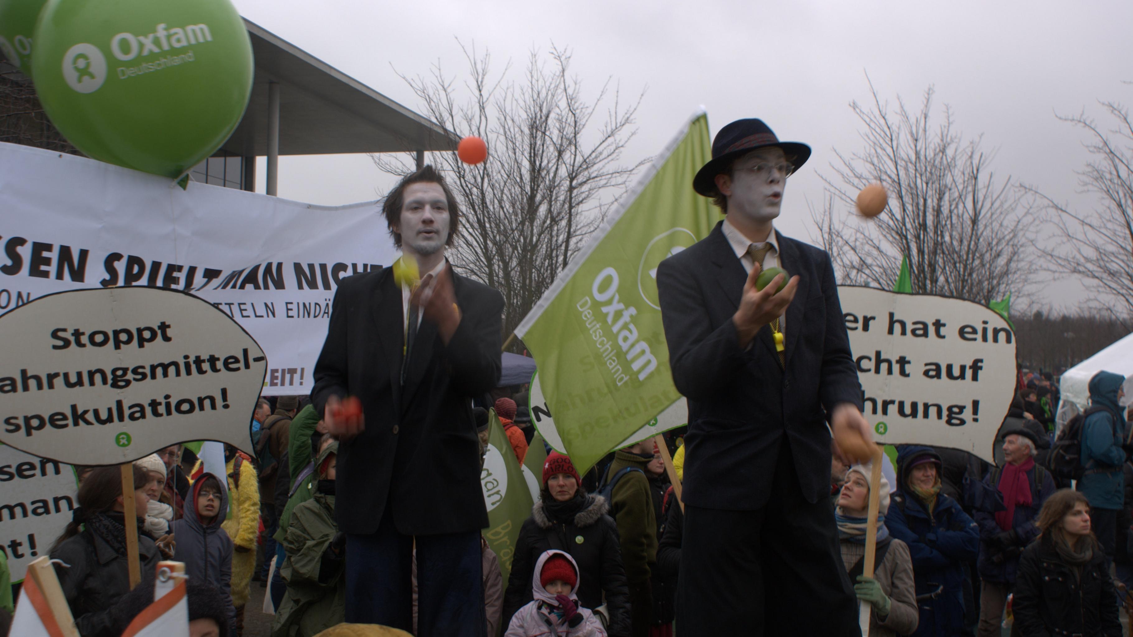 Foto: Oxfam mit Riesenballons und Fahnen mitten im Demonstrationszug