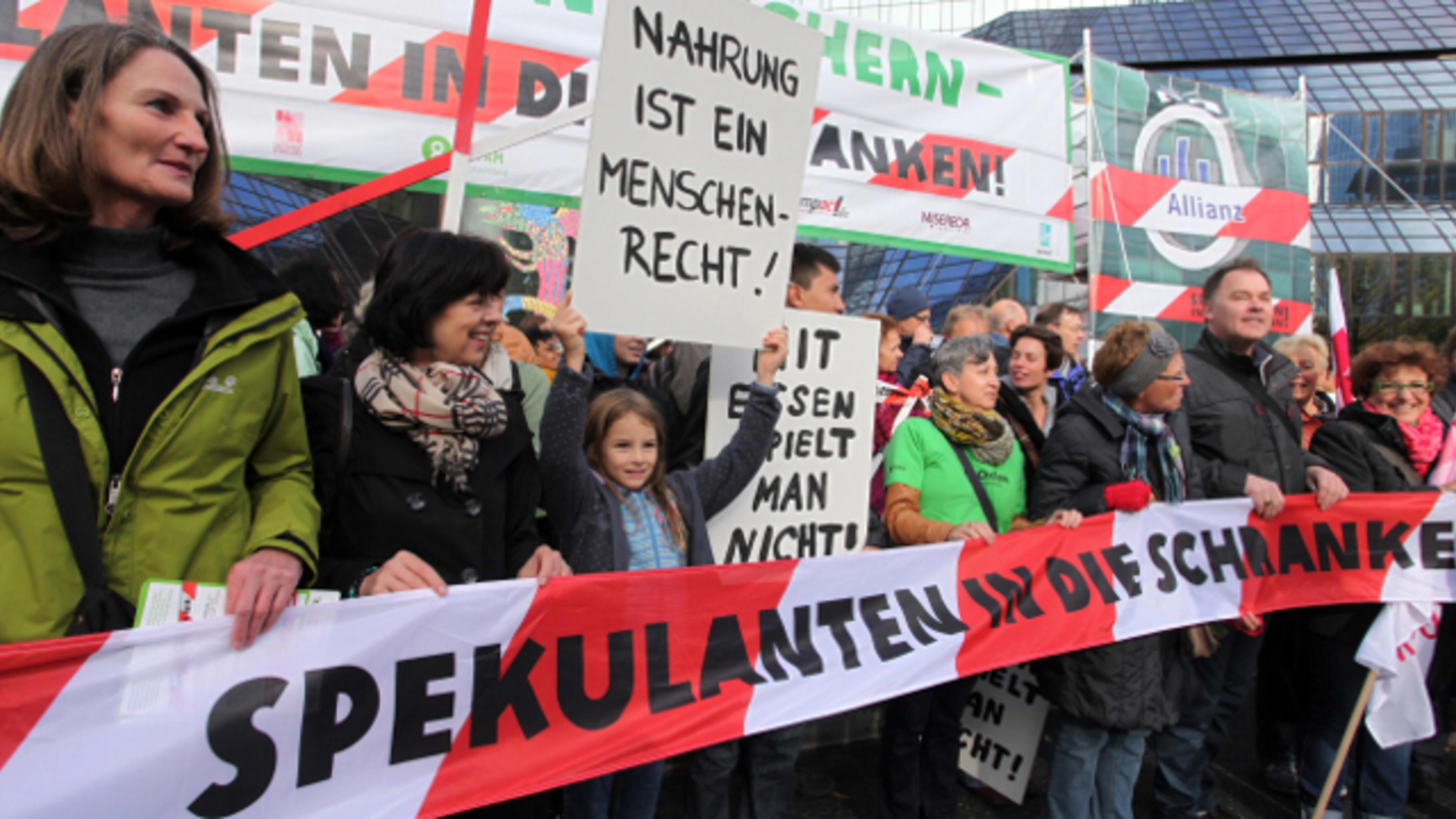 """Demonstranten halten ein Absperrband mit """"Spekulanten in die Schranken"""""""