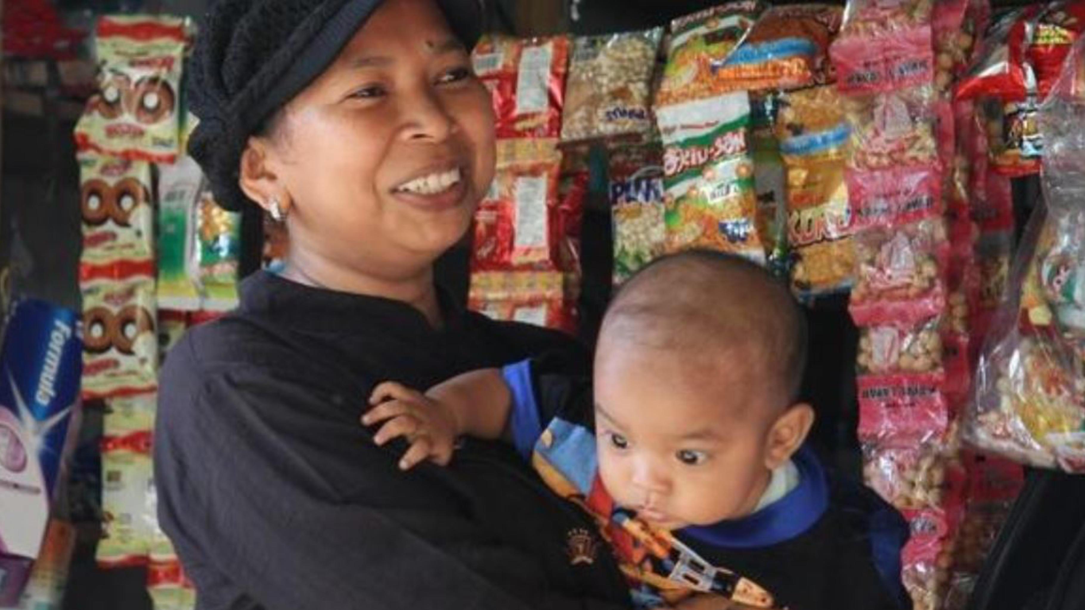 Rusiani mit ihrem Sohn Habil in ihrem Geschäft in Indonesien