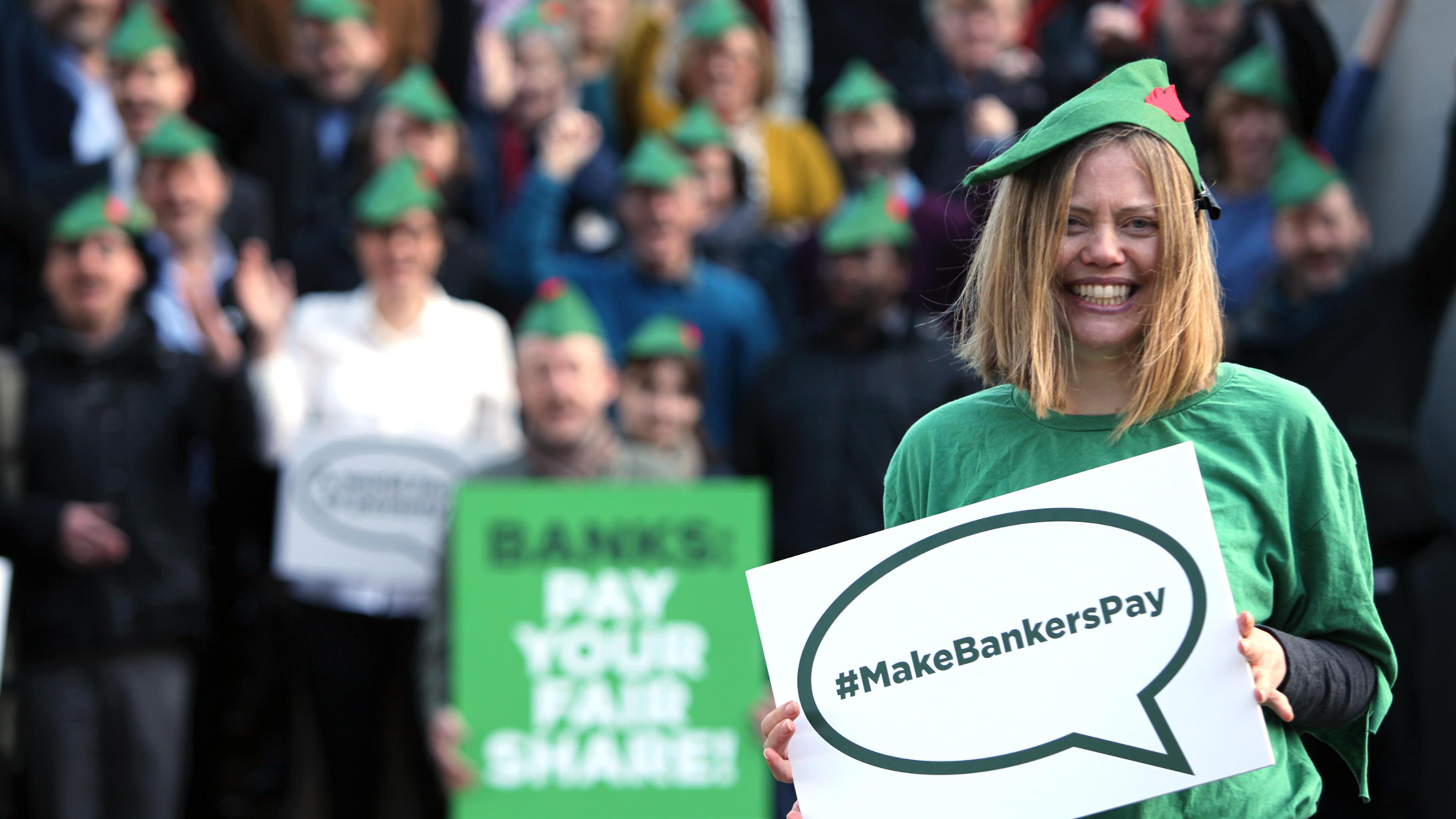 """Als Robin Hood und seine Gefährten verkleidete Aktivist/innen halten Schilder mit der Aufschrift """"Make Bankers Pay"""" und """"Banks: Pay your fair share!"""""""