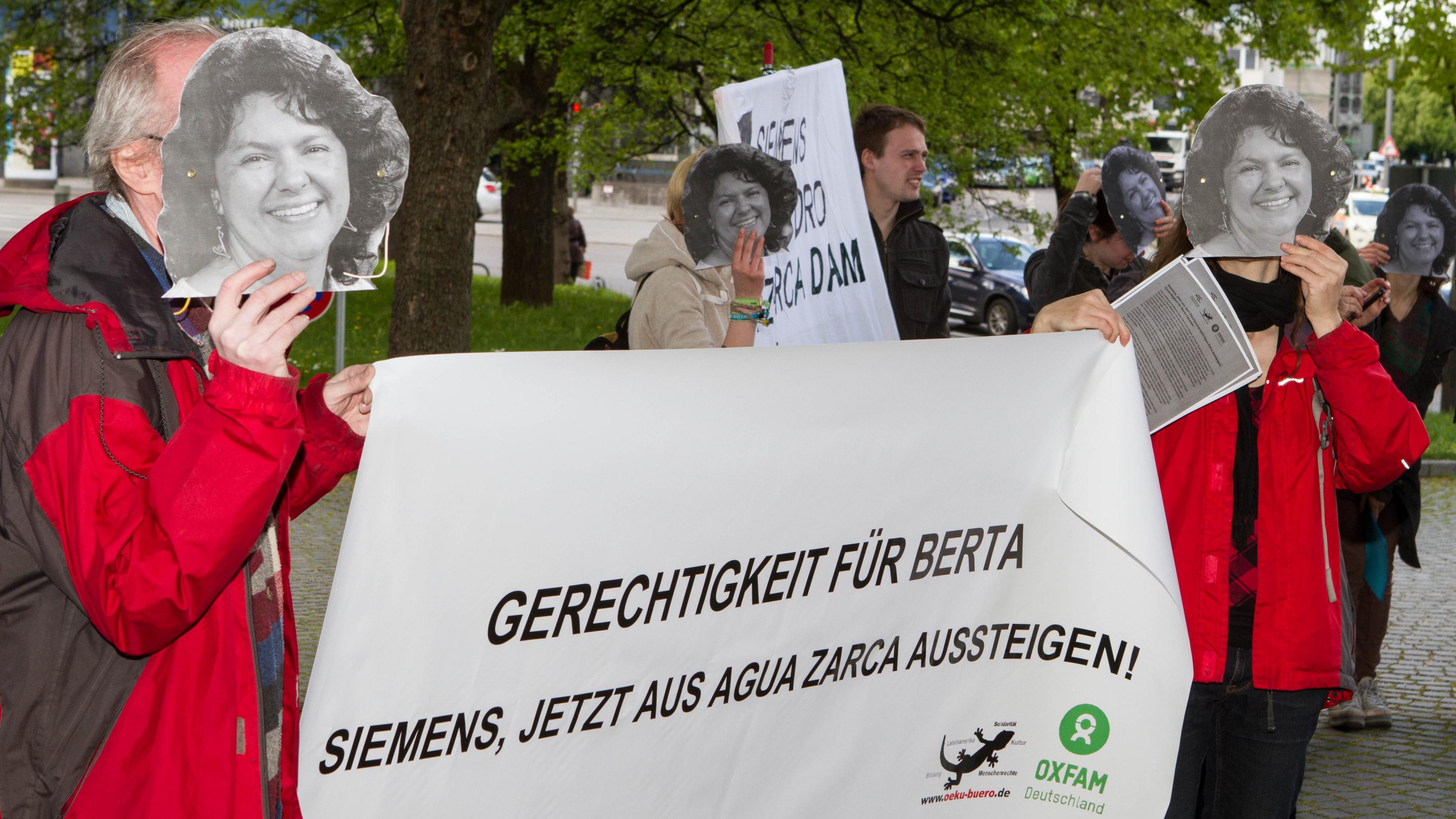 """Demonstrant/innen halten Fotos der ermordeten Berta Cáceres und ein Transparent mit der Aufschrift """"Gerechtigkeit für Berta: Siemens, jetzt aus Agua Zarca aussteigen!"""""""