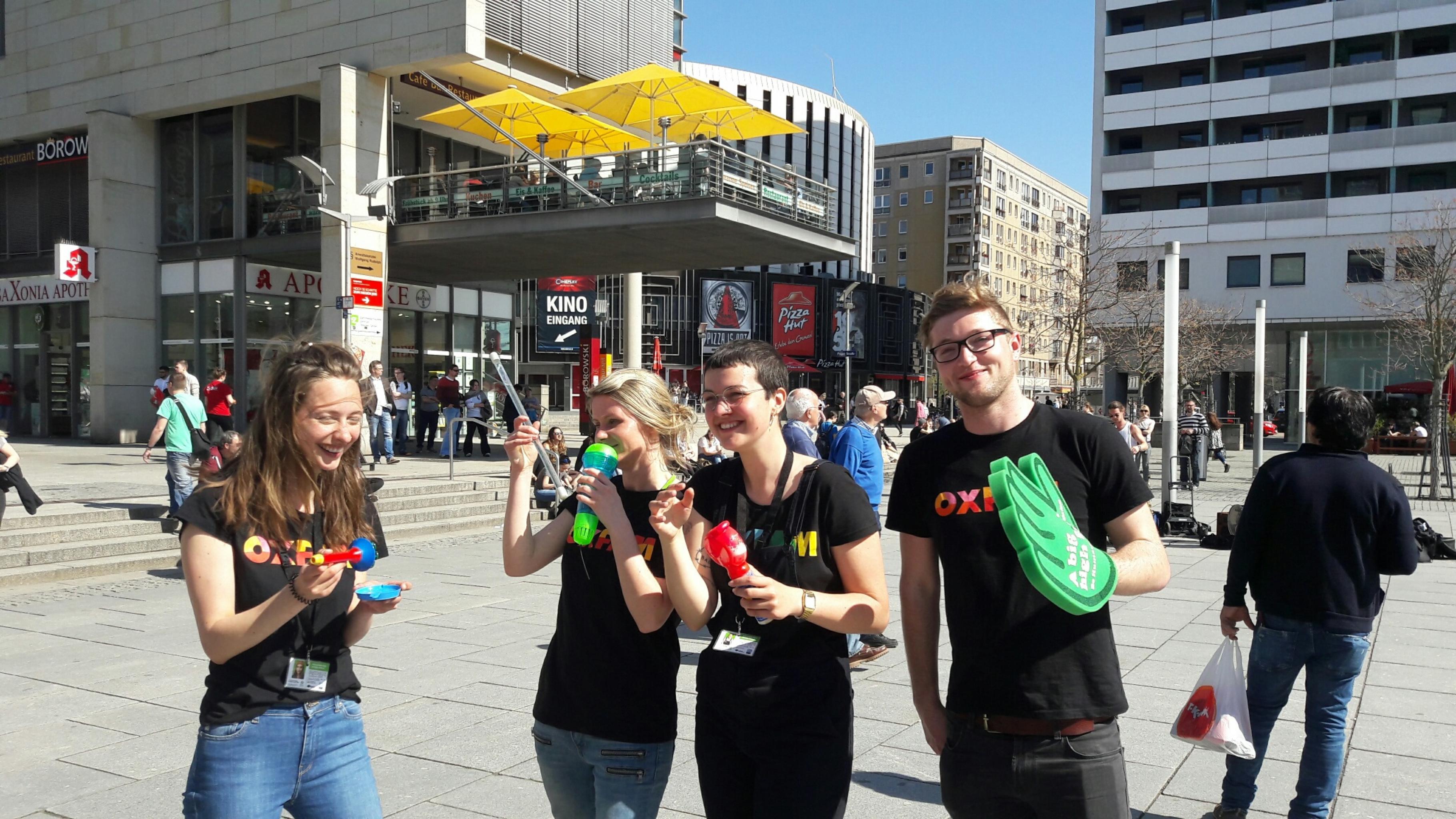 Vier junge Menschen mit Oxfam-T-Shirts bieten Unterhaltung in einer Fußgängerzone
