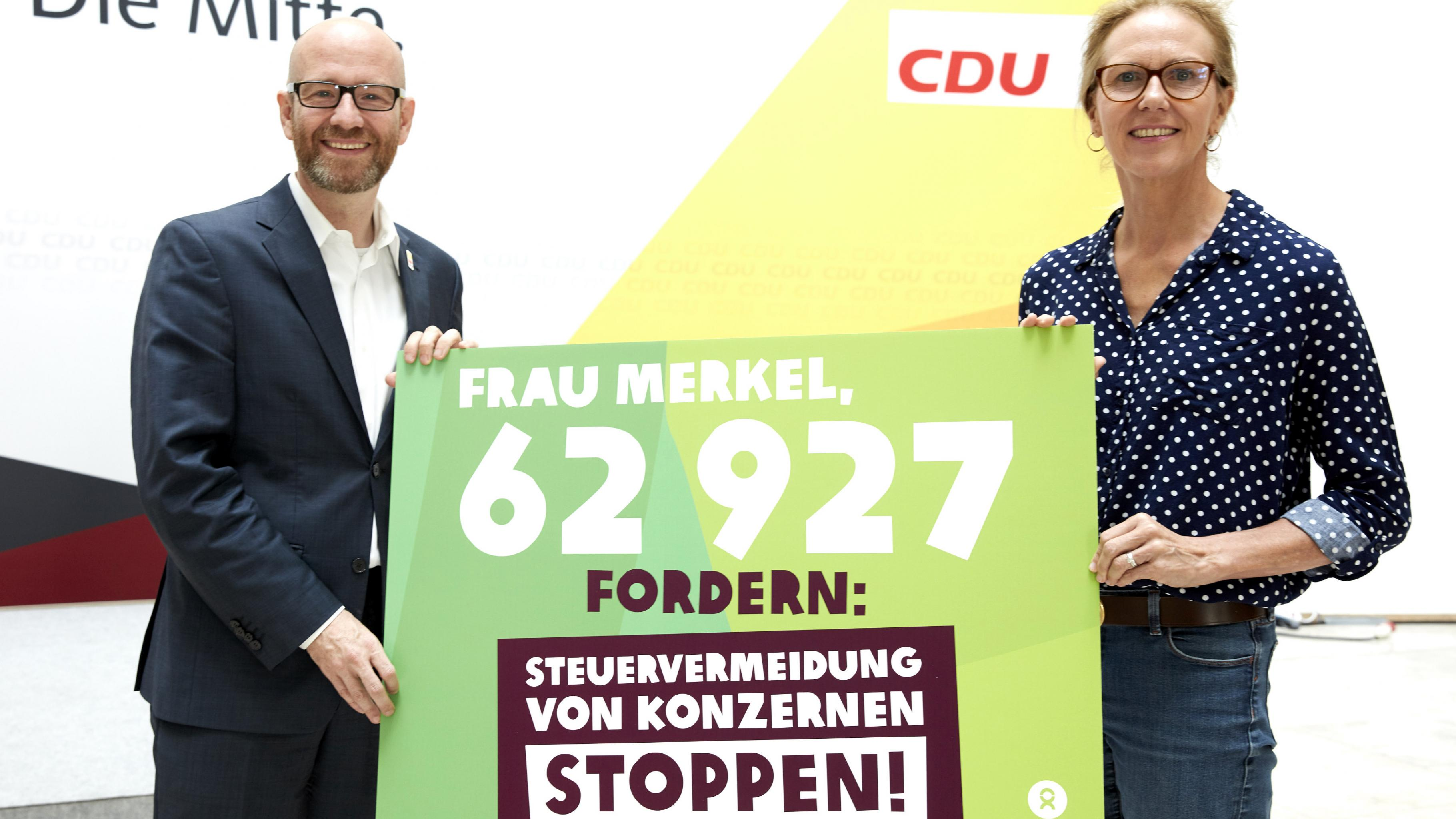 """Marion Lieser und Peter Tauber halten ein Plakat mit der Aufschrift: """"Frau Merkel, 62927 fordern: Steuervermeidung von Konzernen stoppen!"""""""