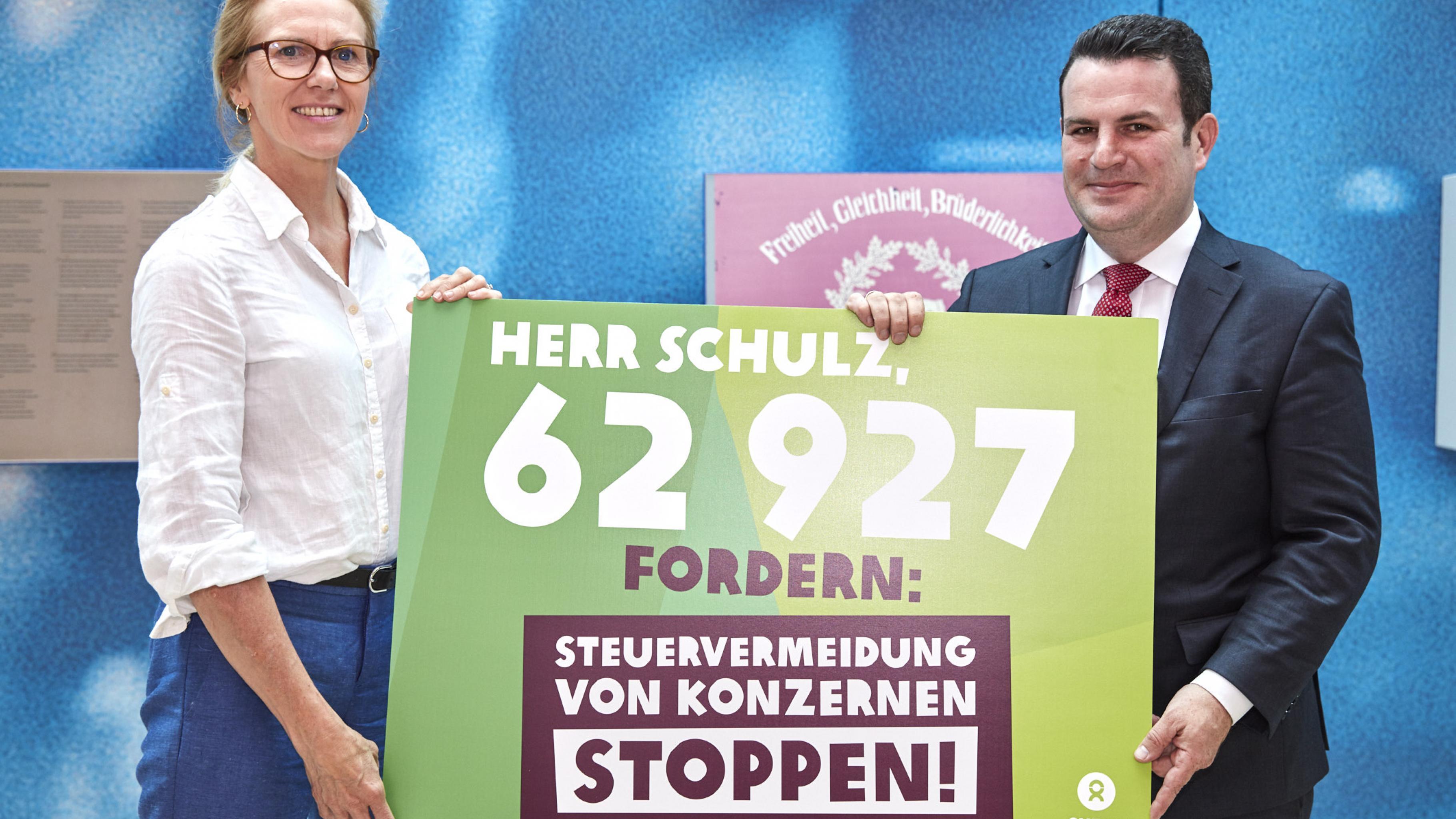 """Marion Lieser und Hubertus Heil halten ein Plakat mit der Aufschrift: """"Herr Schulz, 62927 fordern: Steuervermeidung von Konzernen stoppen!"""""""