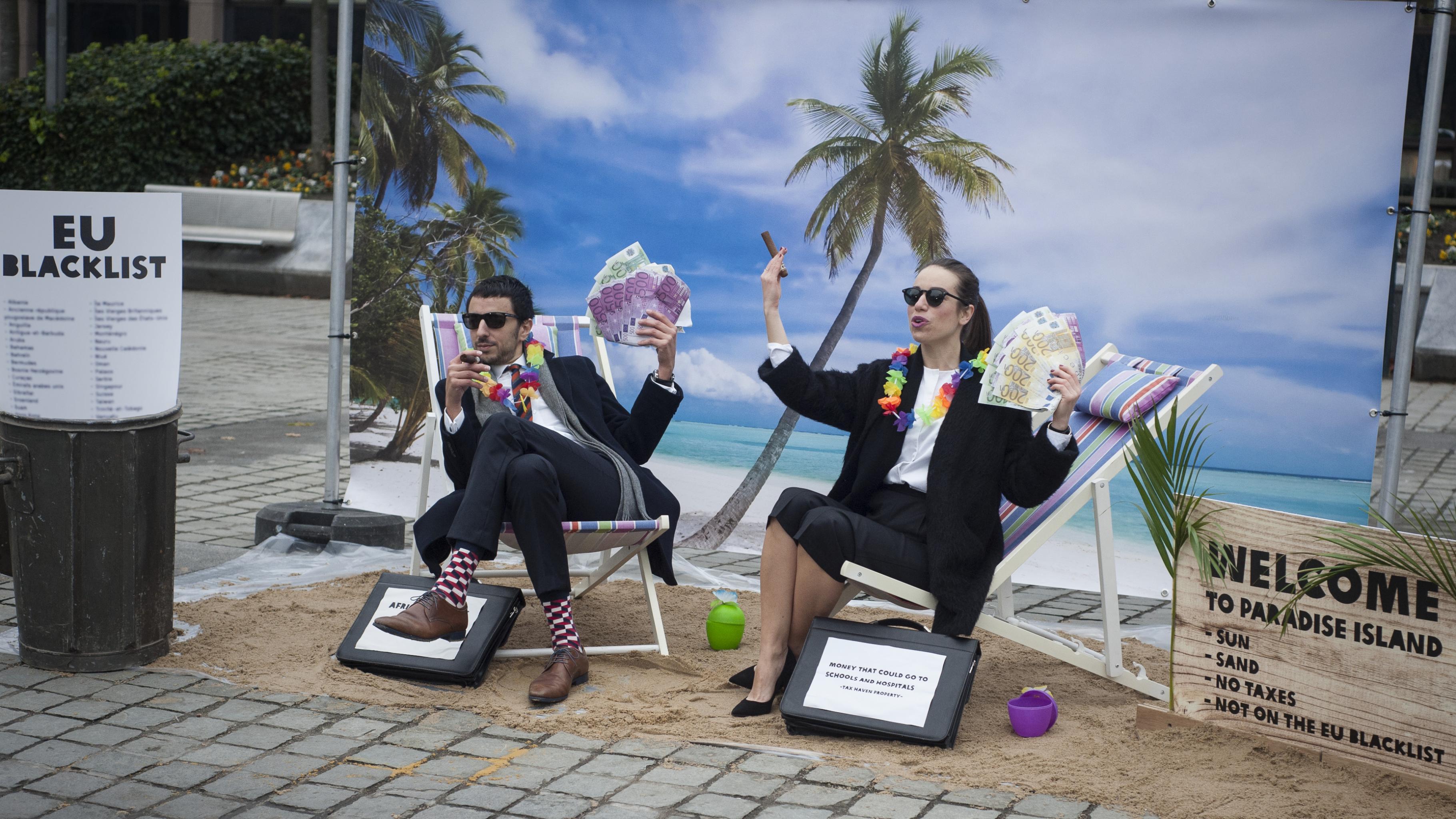 Zwei verkleidete Aktivisten im Anzug mit Sonnenbrille, Zigarren und Geldscheinen sitzen in einer karibischen Kulisse und freuen sich darüber, dass ihre Steueroase nicht auf der Schwarzen Liste der EU steht.