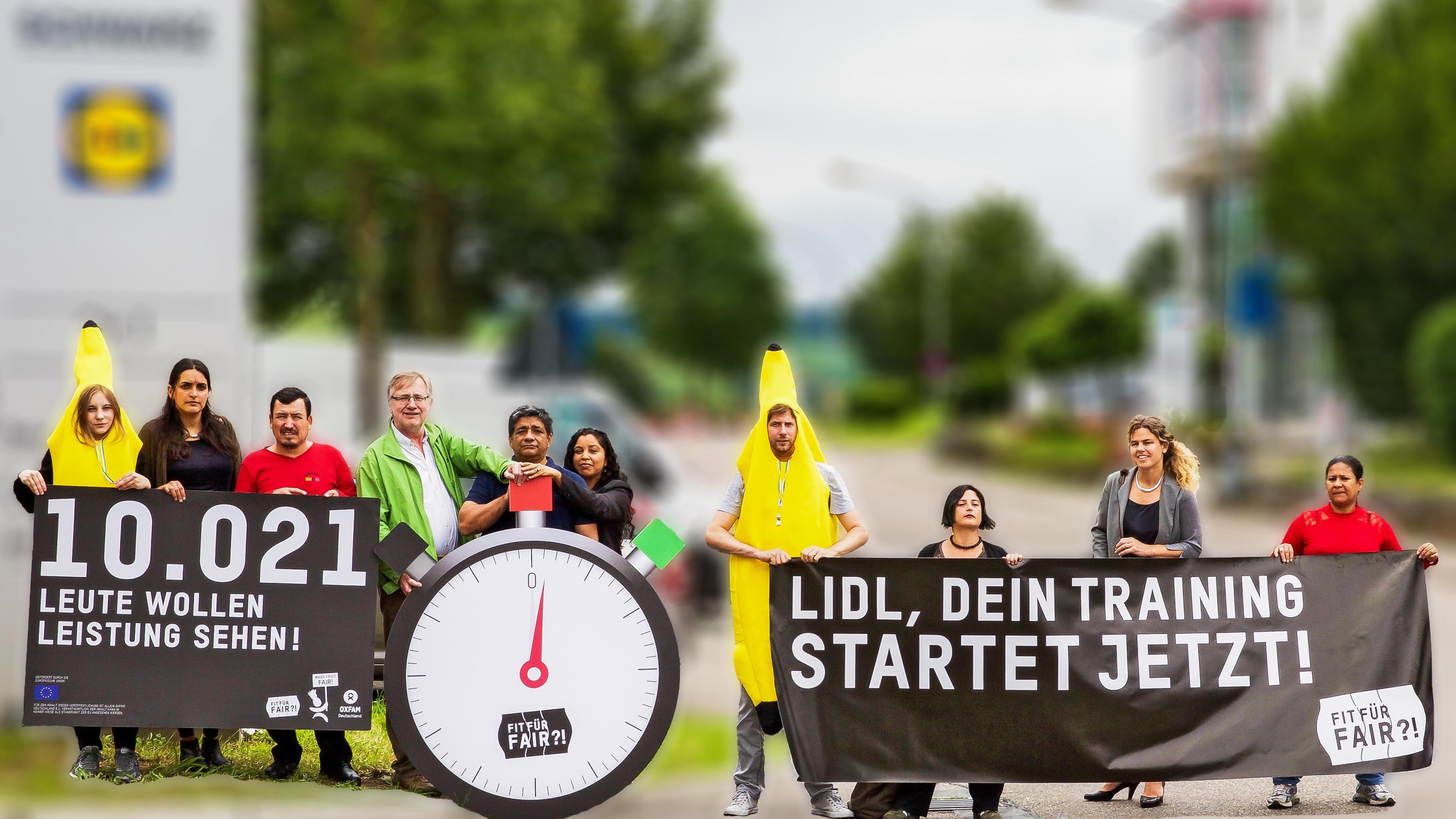 """Aktivistinnen und Aktivisten, teilweise in Bananen-Kostümen, vor der Lidl-Konzernzentrale, mit Bannern """"10021 Leute wollen Leistung sehen!"""", """"Lidl, dein Training startet jetzt!"""" und einer großen Stoppuhr mit der Aufschrift """"Fit für Fair?!""""."""