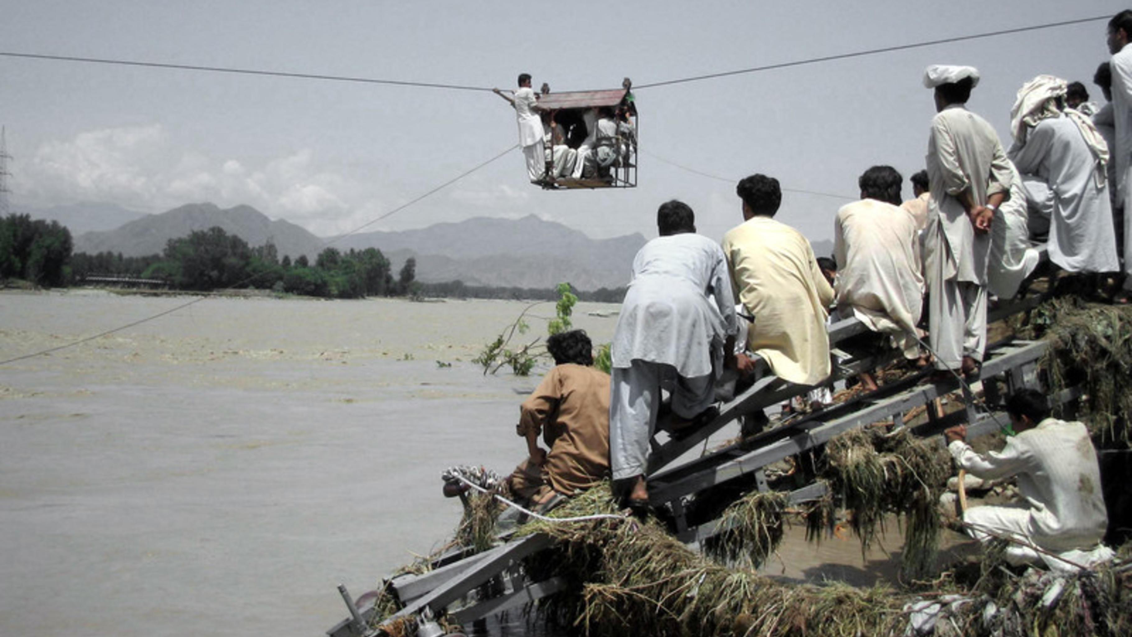 Foto: Menschen nutzen eine Seilbahn zur Flucht vor dem Wasser.