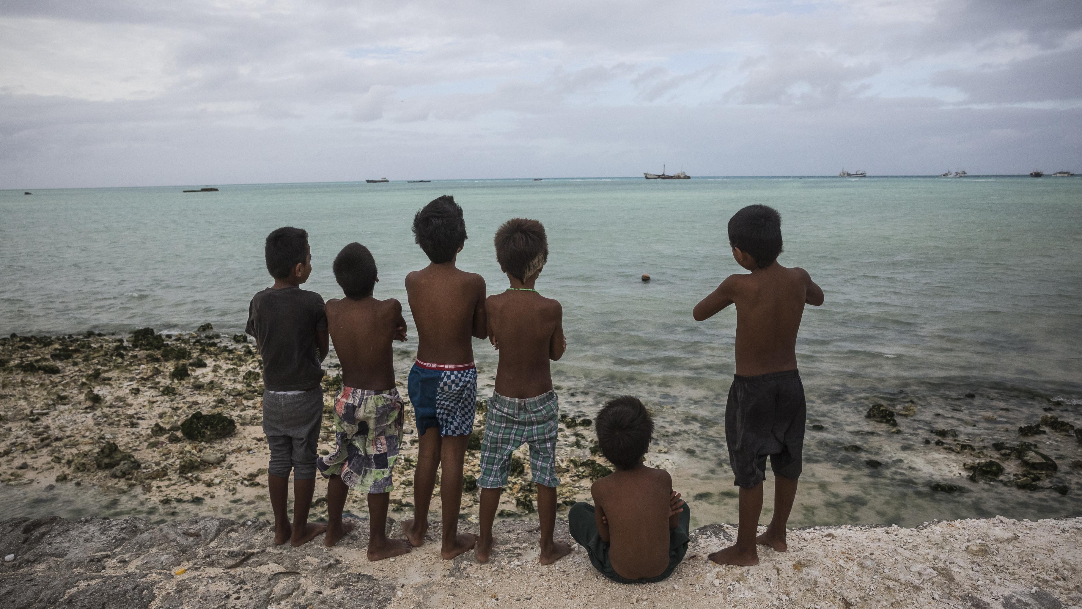 Ein Kind sitzt und fünf Kinder stehen auf einem Damm und blicken auf das Meer.