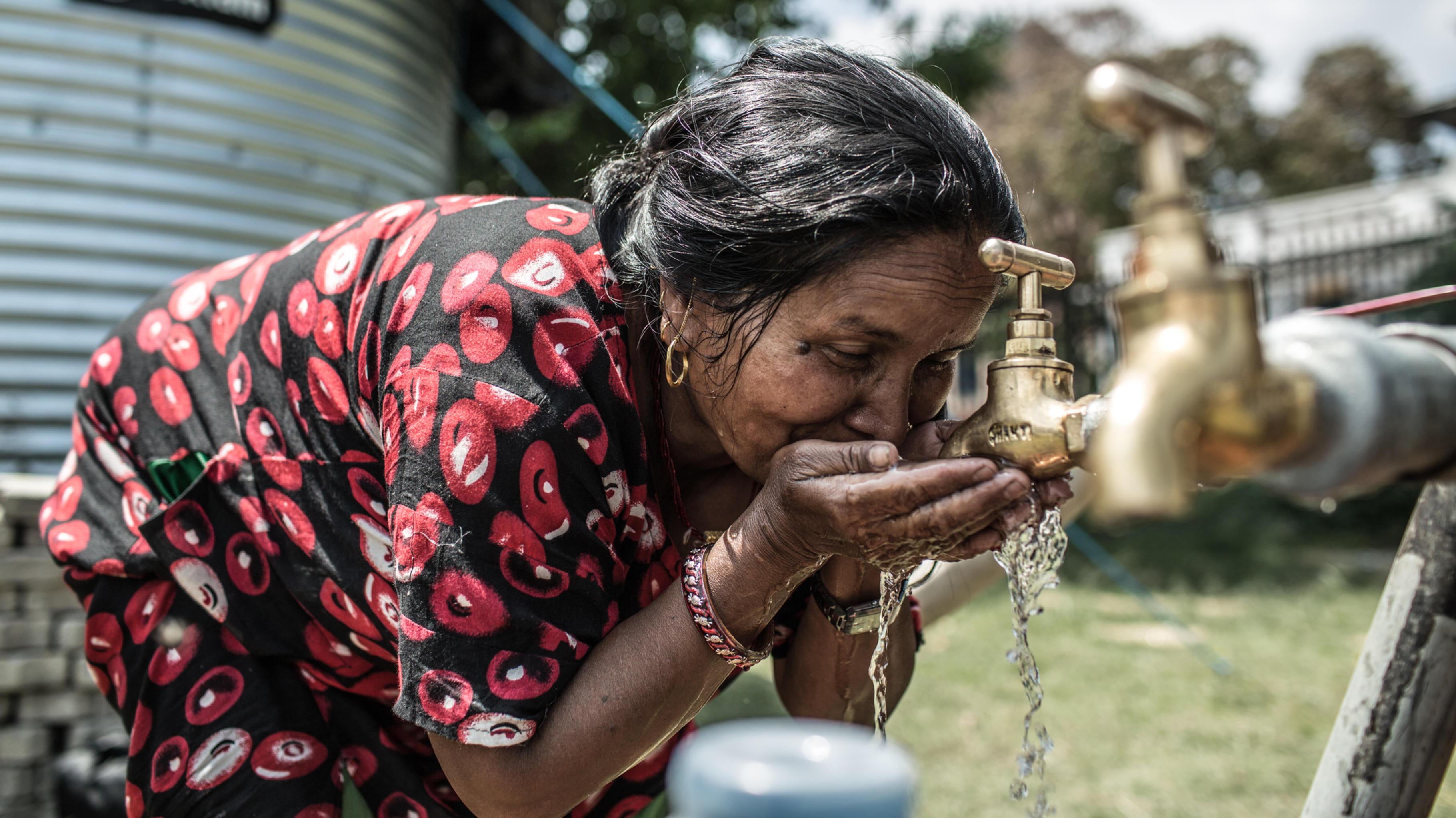 Eine Frau in Nepal trinkt aus deinem Wassertank von Oxfam.