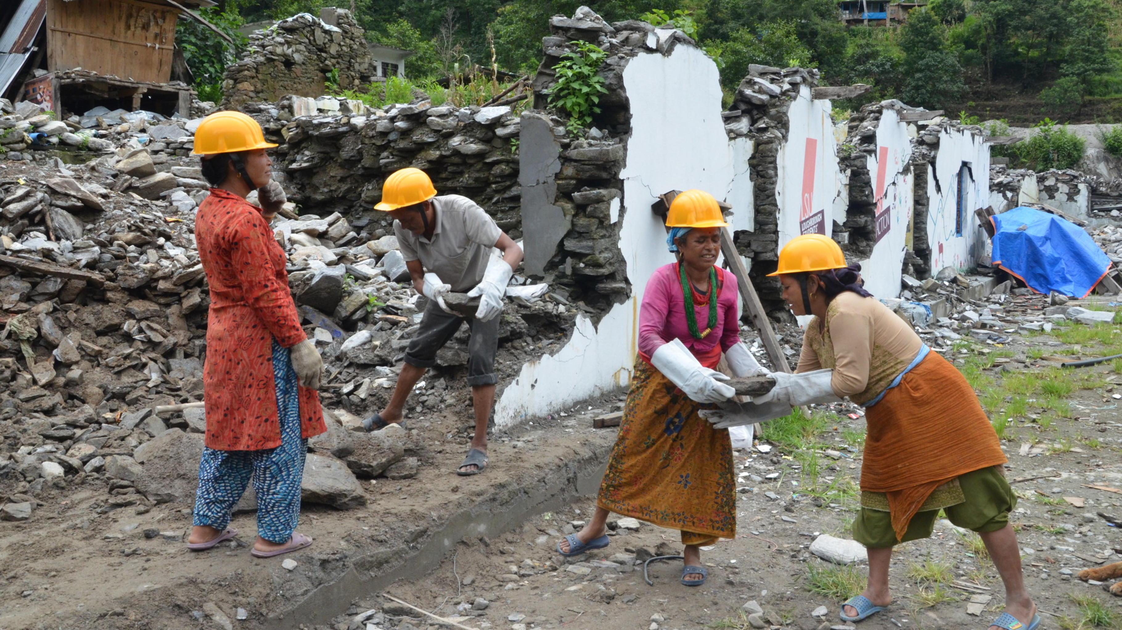 Frauen bauen eine Strasse, die vom Erdbeben in Nepal zerstört wurde.