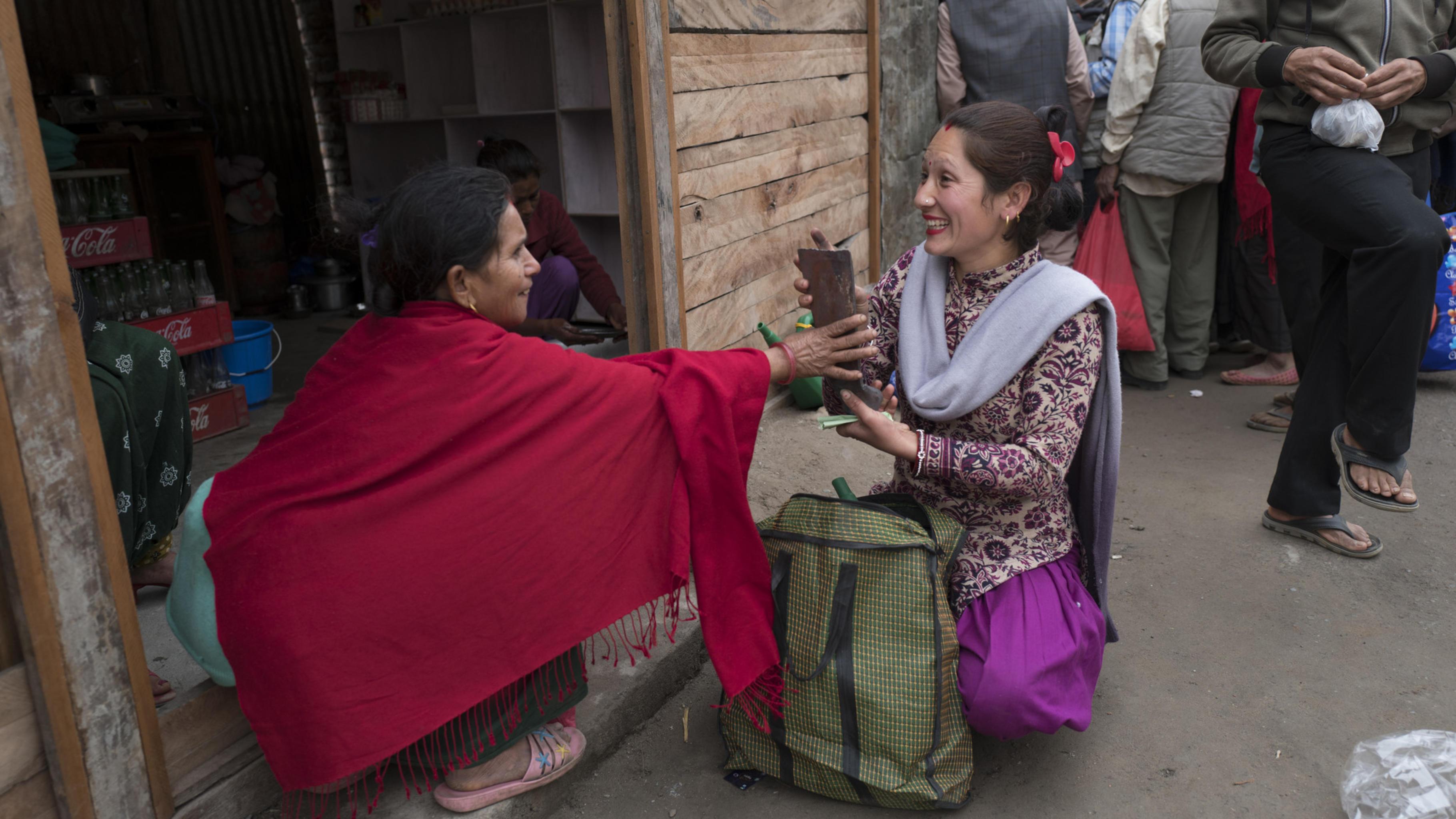 Eine Frau kauft eine Gartenhacke in einem Geschäft, Nepal