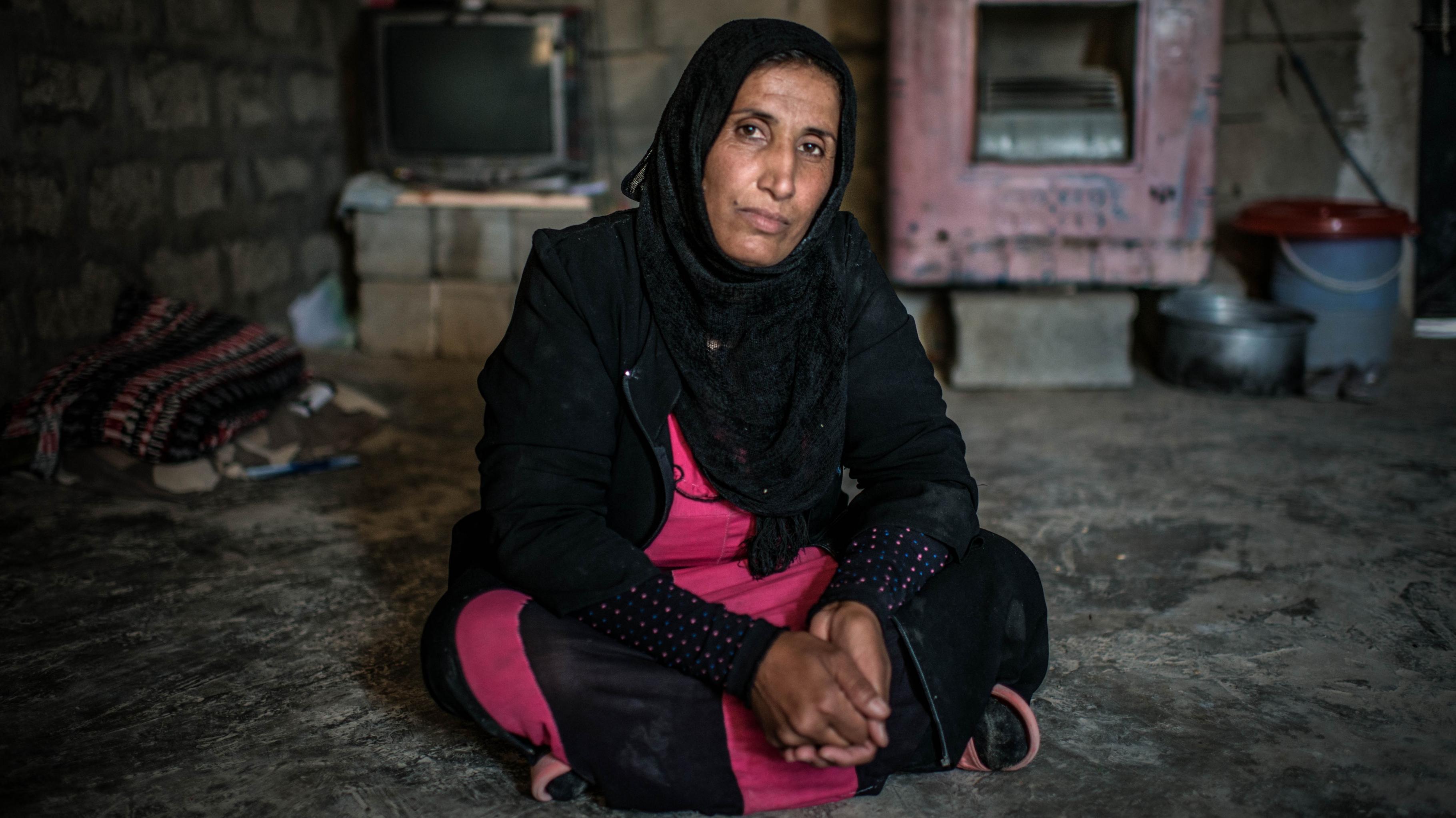 Wafaa sitzt auf dem Boden des kleinen Hauses, das sie derzeit mit ihrer Familie bewohnt.