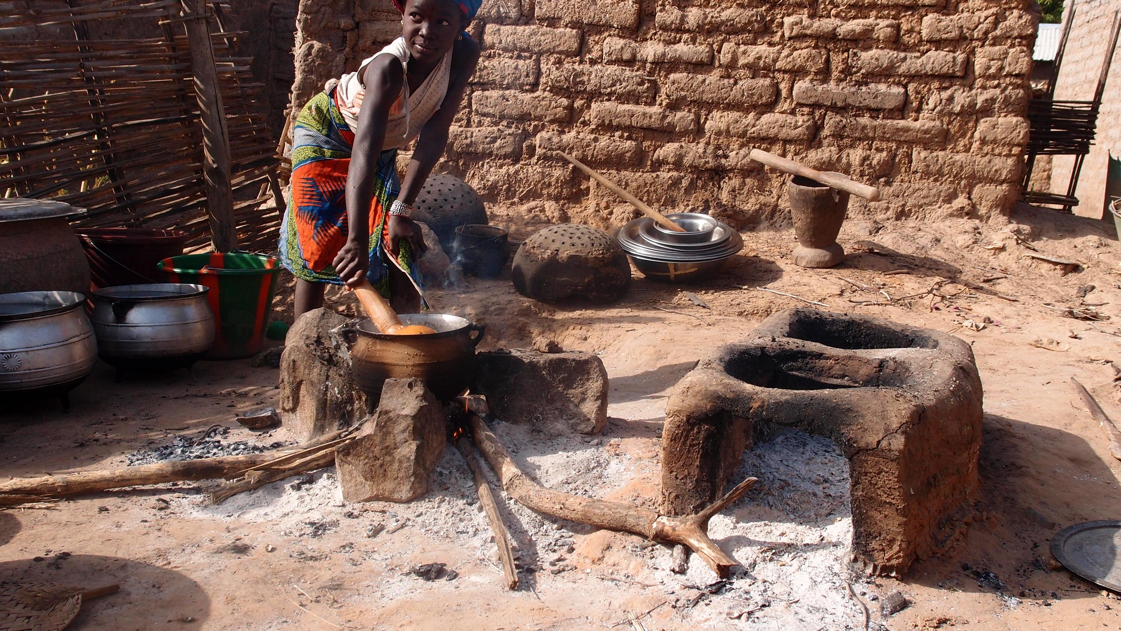 Mädchen steht an einer Feuerstelle, auf der ein Topf zum Kochen steht