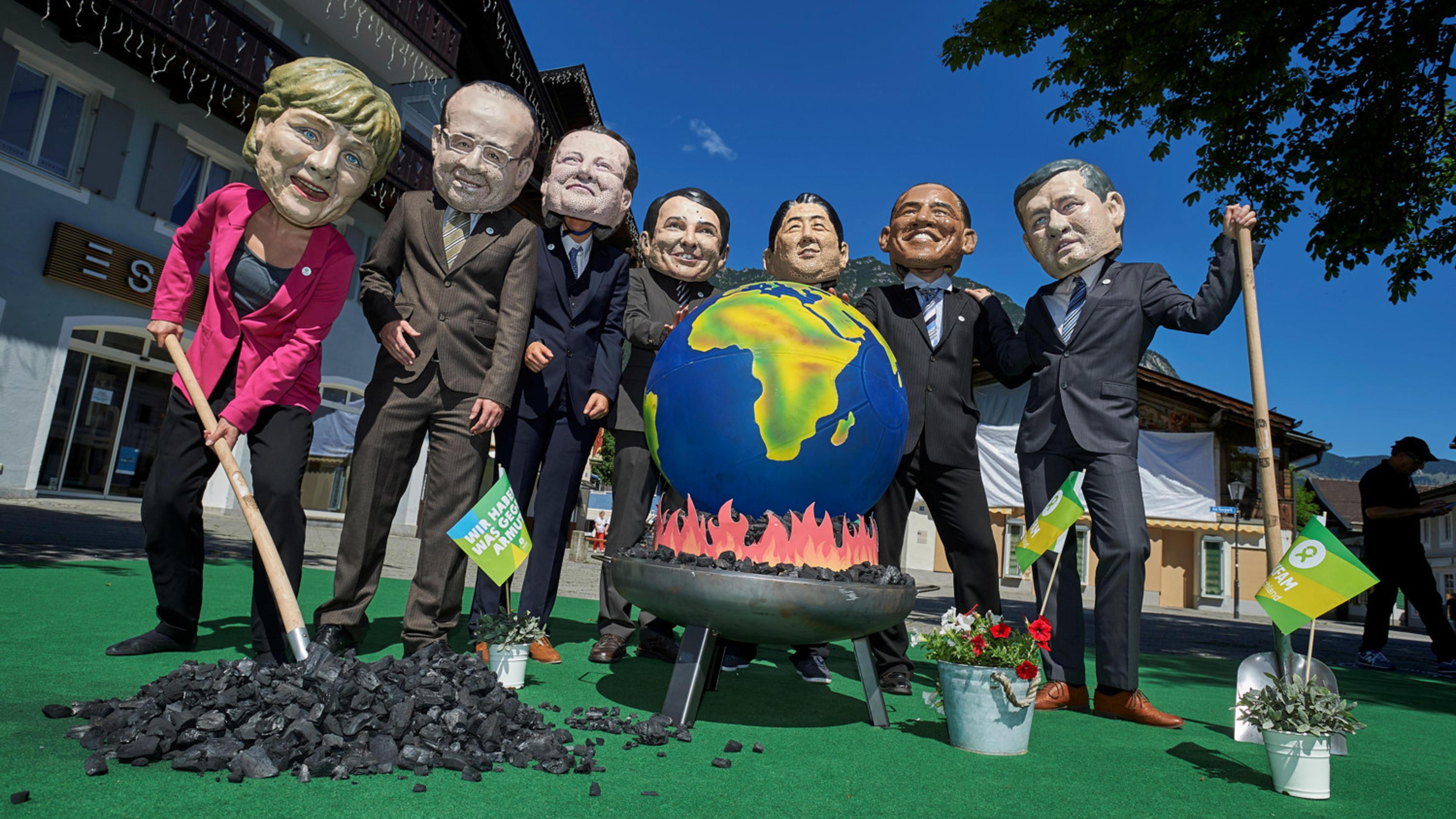 Als G7 verkleidete Aktivist/innen grillen eine Weltkugel mit Kohle