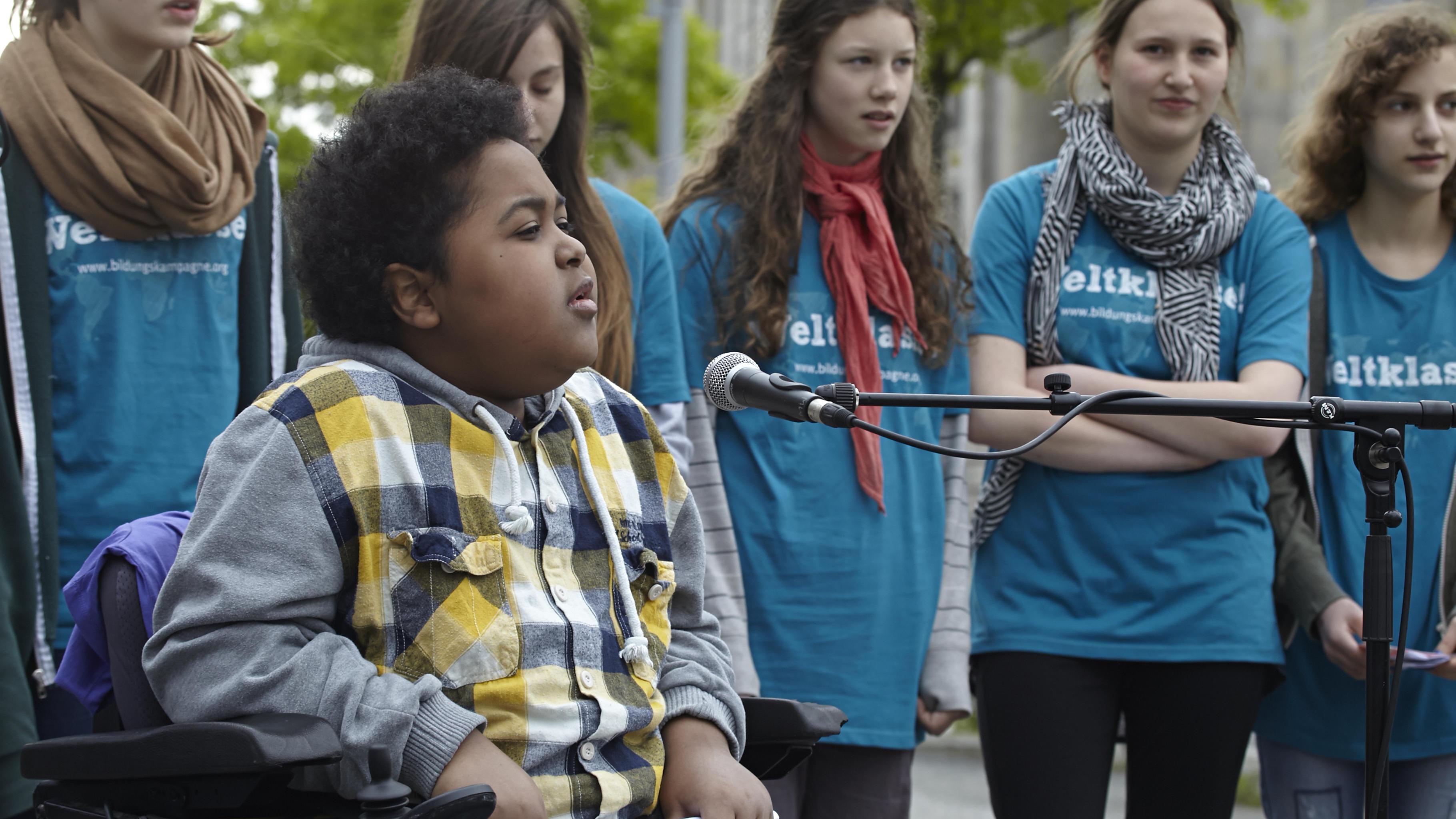 Schüler/innen, Rollstuhl-Rapper Graf Fidi und Bundestagsabgeordnete reißen Mauer
