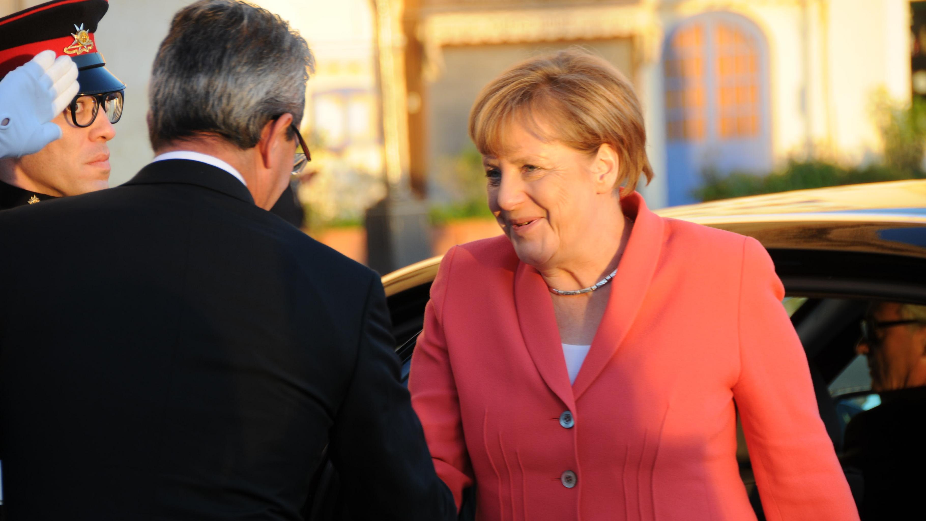 Angela Merkel steigt aus dem Auto aus und wird begrüßt