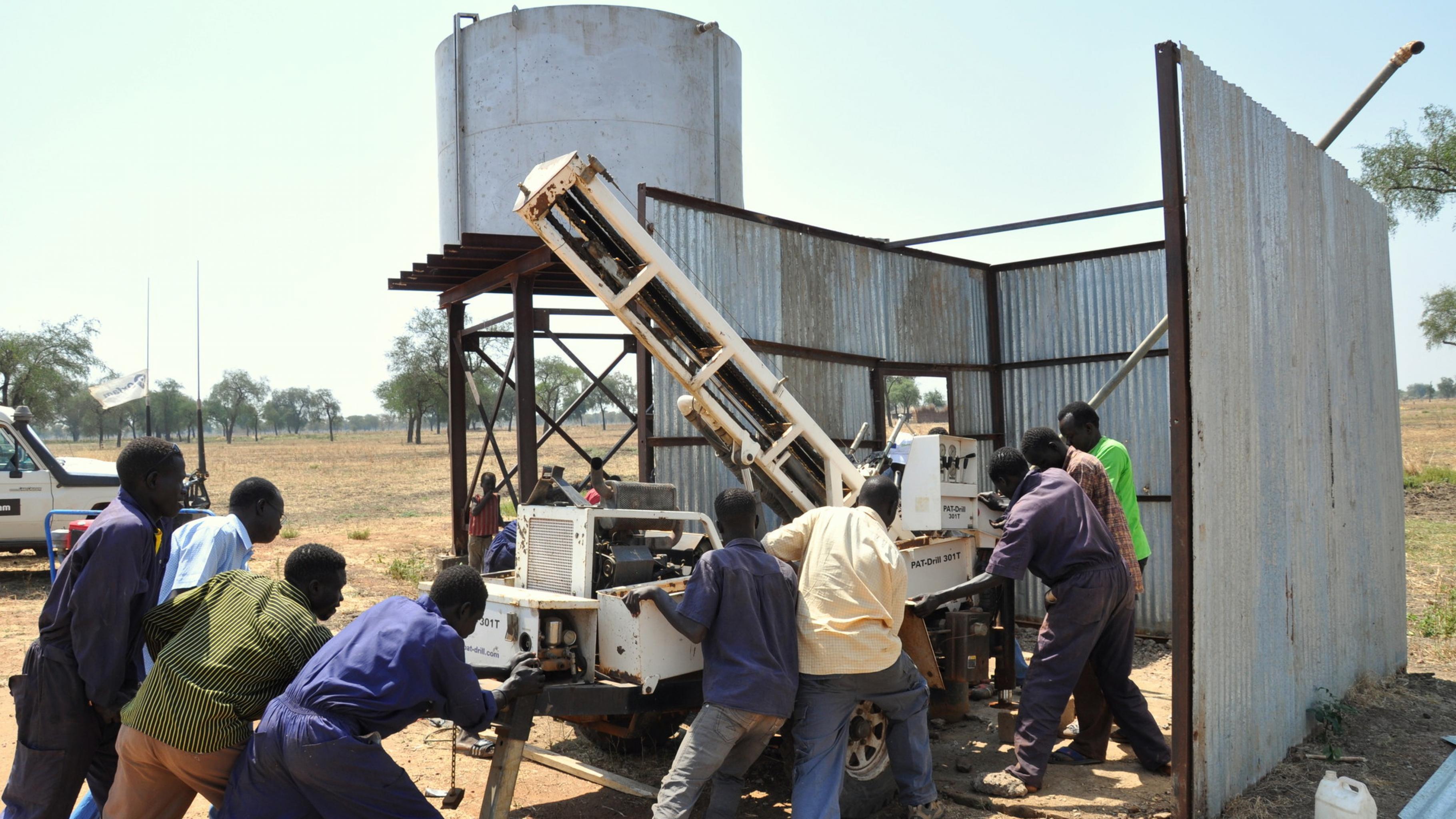 Foto: Arbeiter beim Instandsetzen eines Bohrlochs für sauberes Wasser.