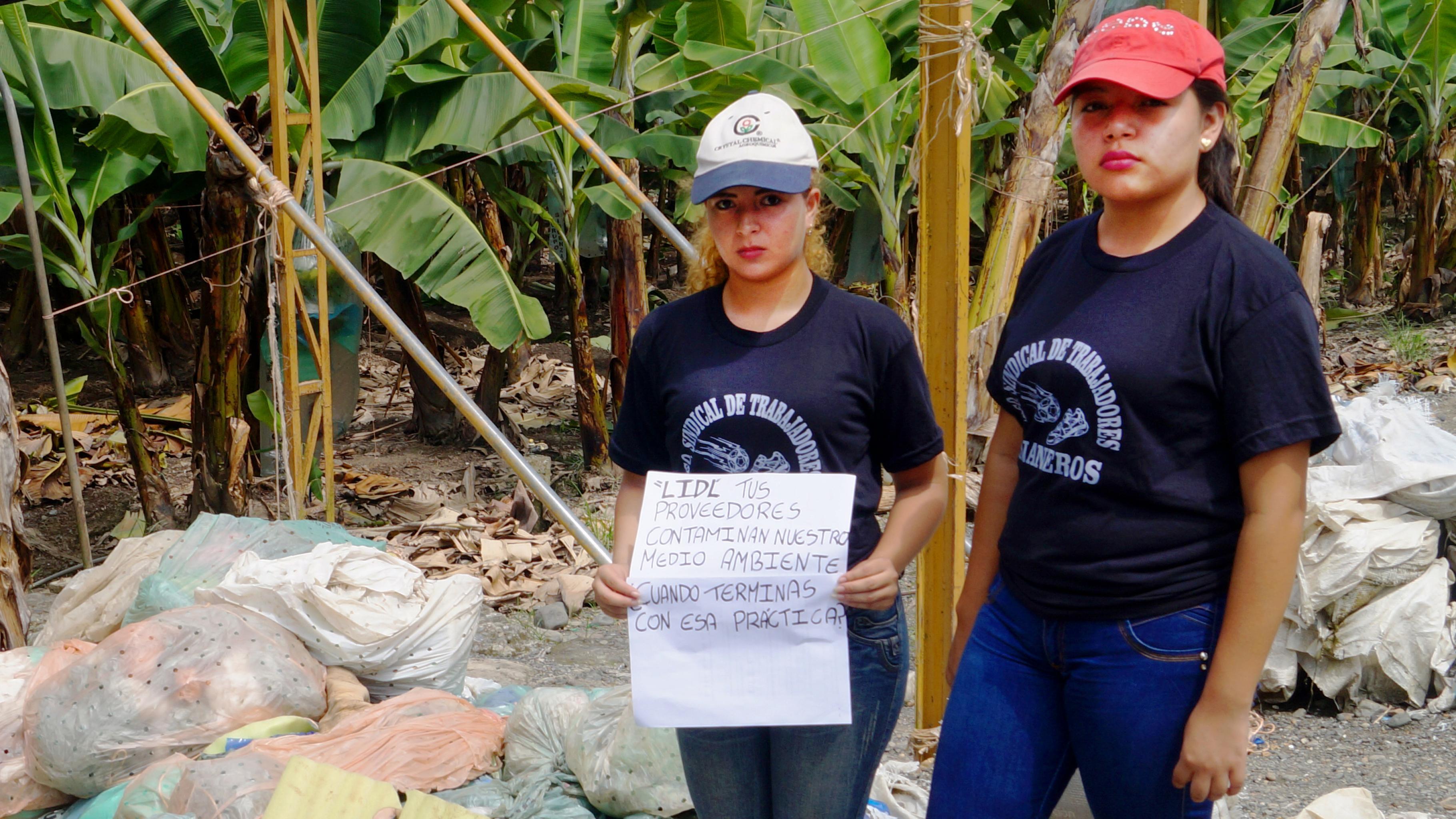 """Zwei Frauen stehen an einer Straße vor einer Bananenplantage. Eine hält ein Plakat mit der Aufschrift: """"Lidl, tus proveedores contaminan nuestro medio ambiente – cuando terminas con esa práctica?"""""""
