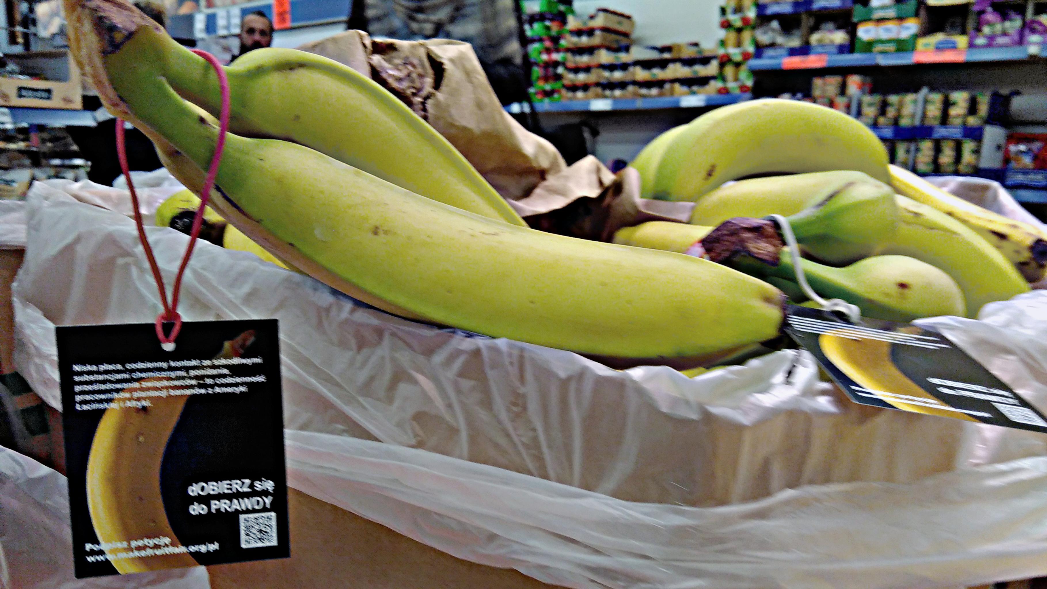 Anhänger mit Informationszetteln hängen an Bananen in Kisten im Supermarkt