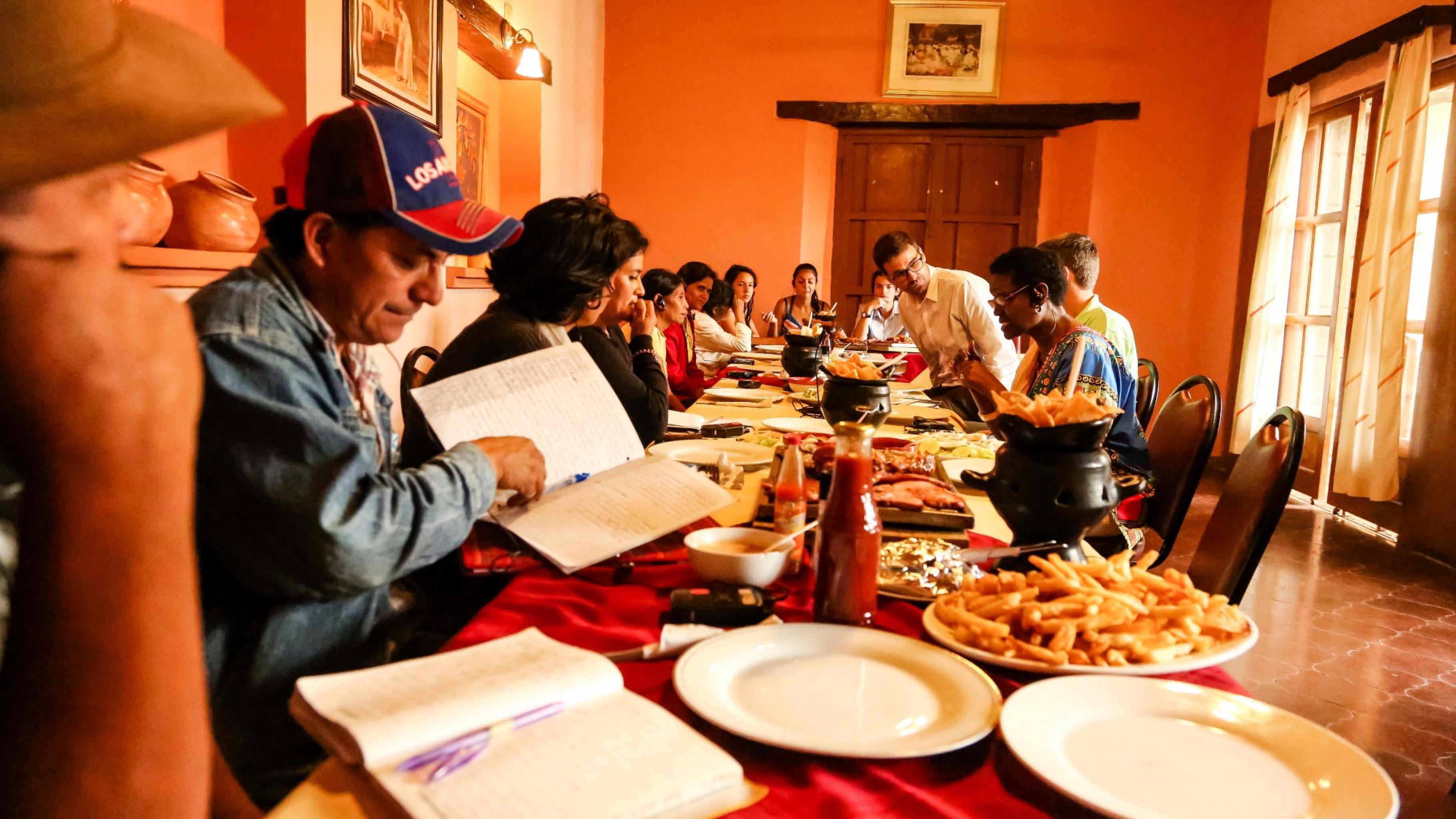Frauen und Männer sitzen mit Notizbüchern in einem Restaurant und beraten sich.