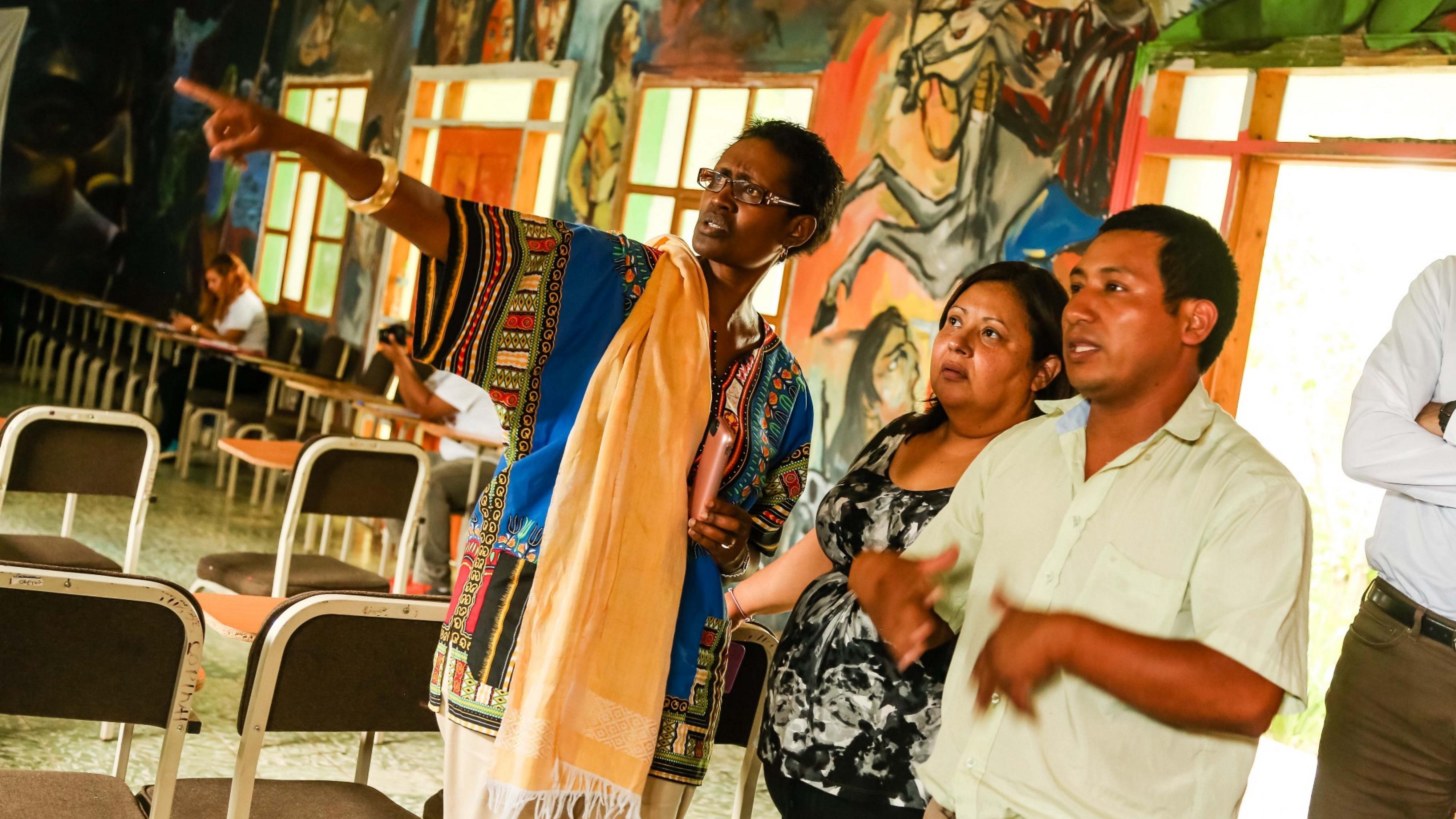 Ein Mann erklärt Winnie Byanyima die reichverzierten Wände in einem ansonsten sehr schlichten Versammlungsraum.