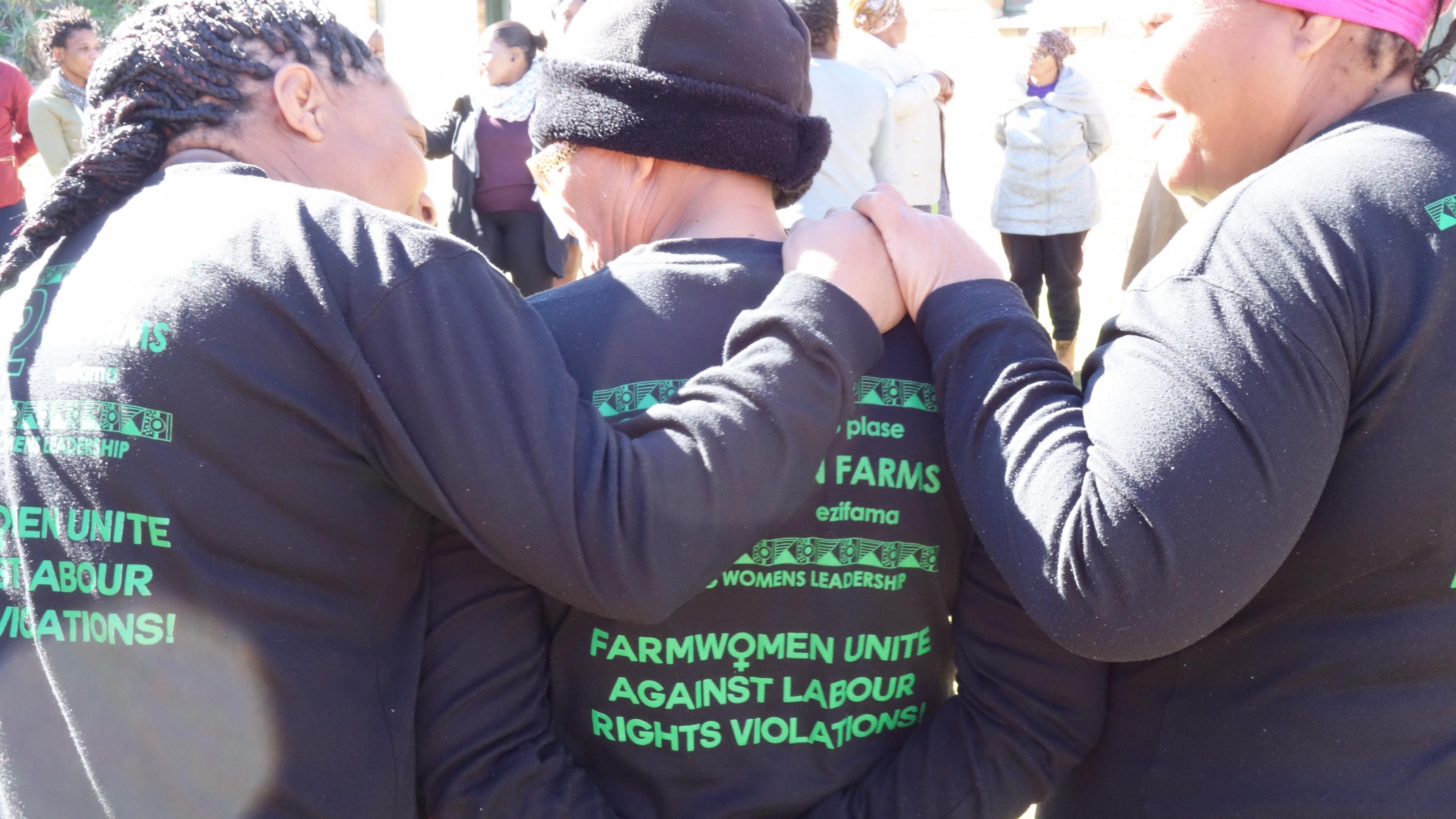 """Drei Frauen stehen nebeneinander, die Hände auf die Schultern gelegt. Auf ihren Pullovern steht: """"Farmwomen unite against labour rights violations!"""""""