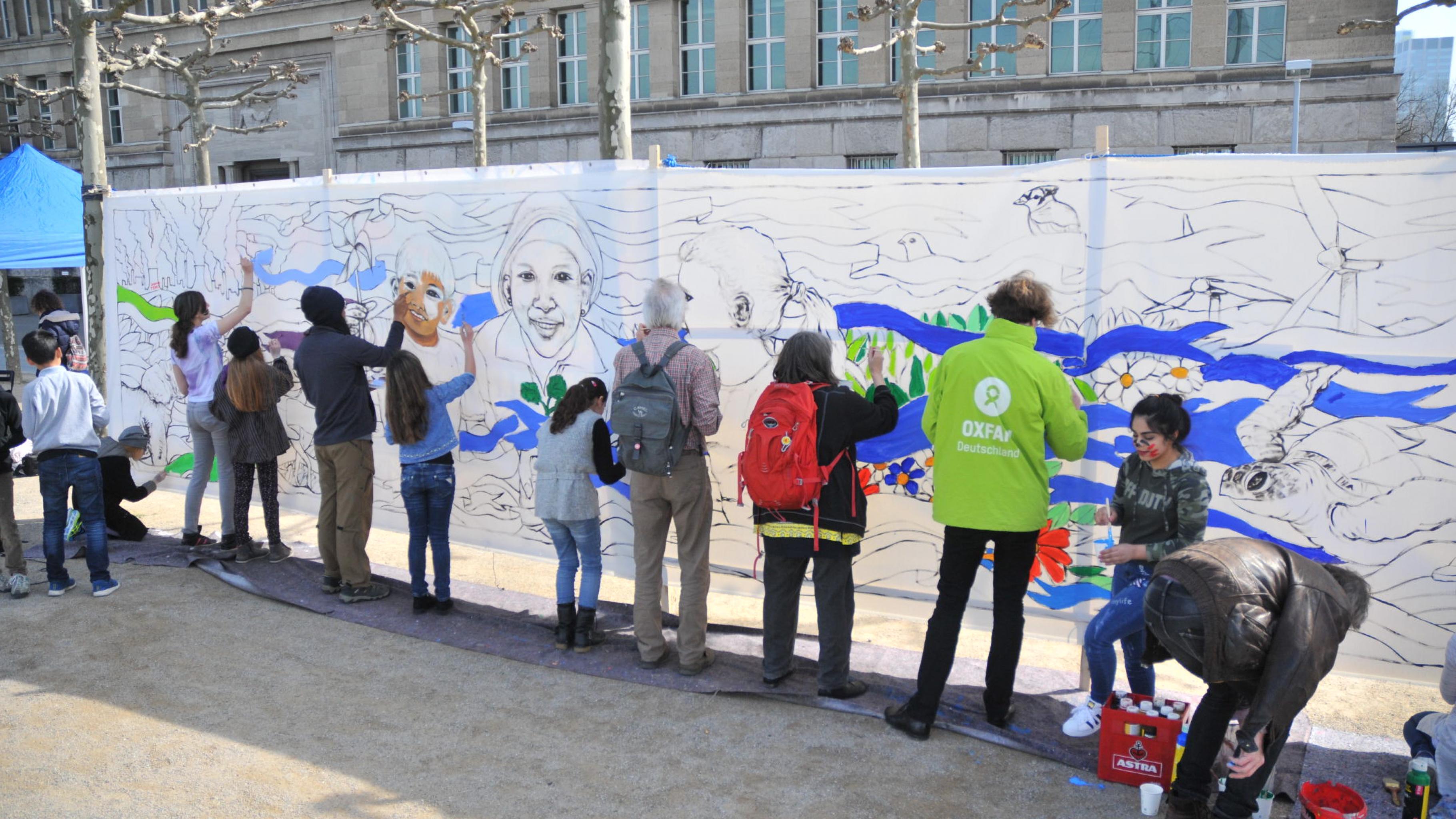 Ein Dutzend Erwachsene und Kinder malen an einer noch weitgehend weißen Leinwand.