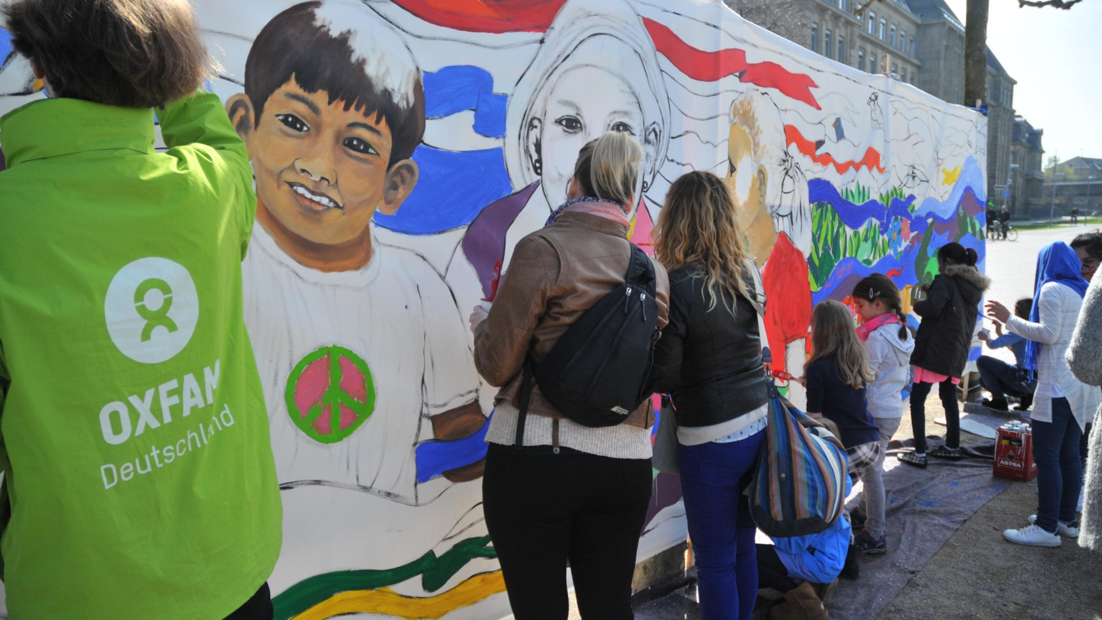 Kinder und Erwachsene malen auf einer 8x2 Meter großen Leinwand an einem halb fertigen Bild.