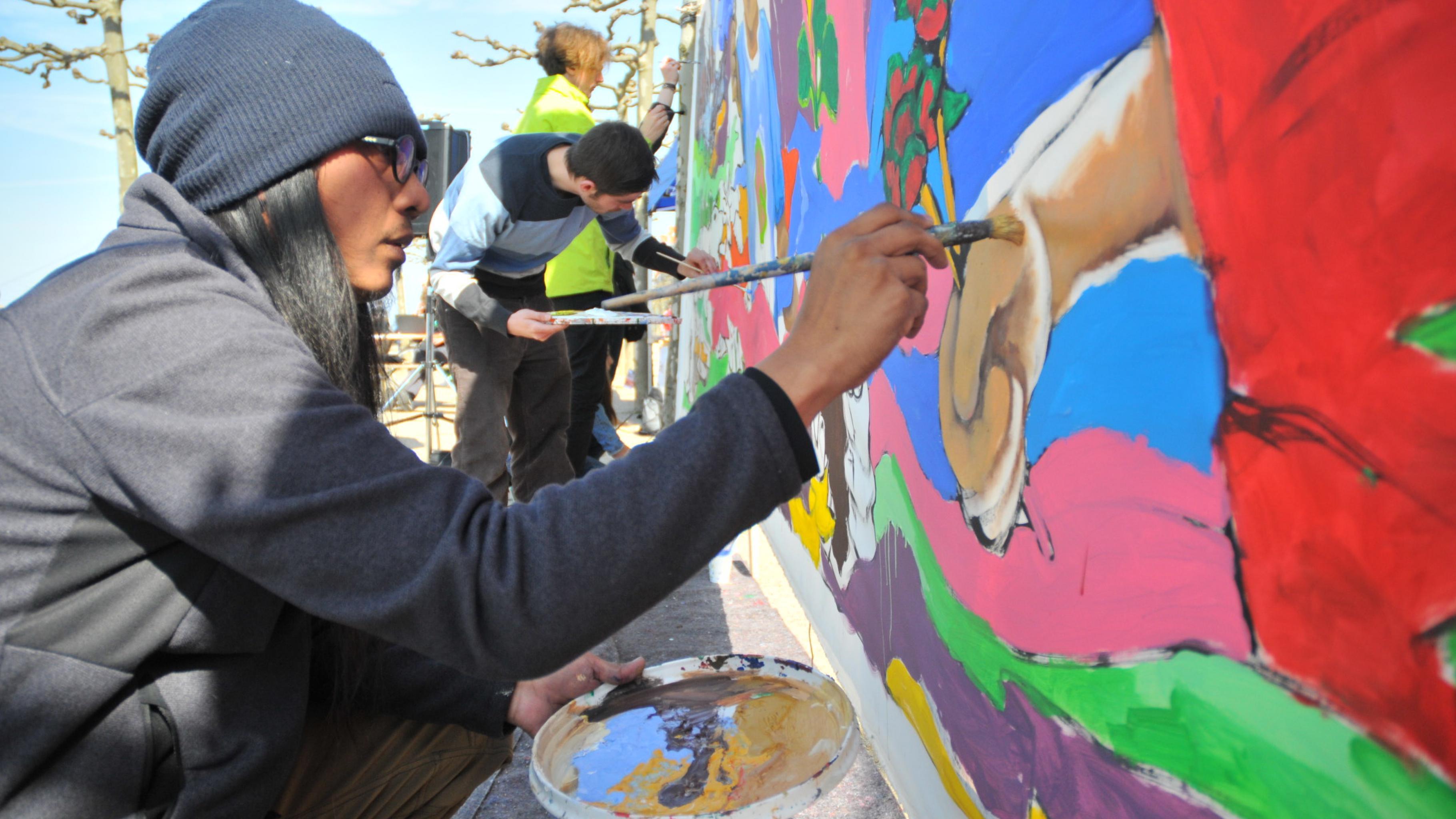 AG Saño malt an dem fast fertigen Bild auf einer riesigen Leinwand.