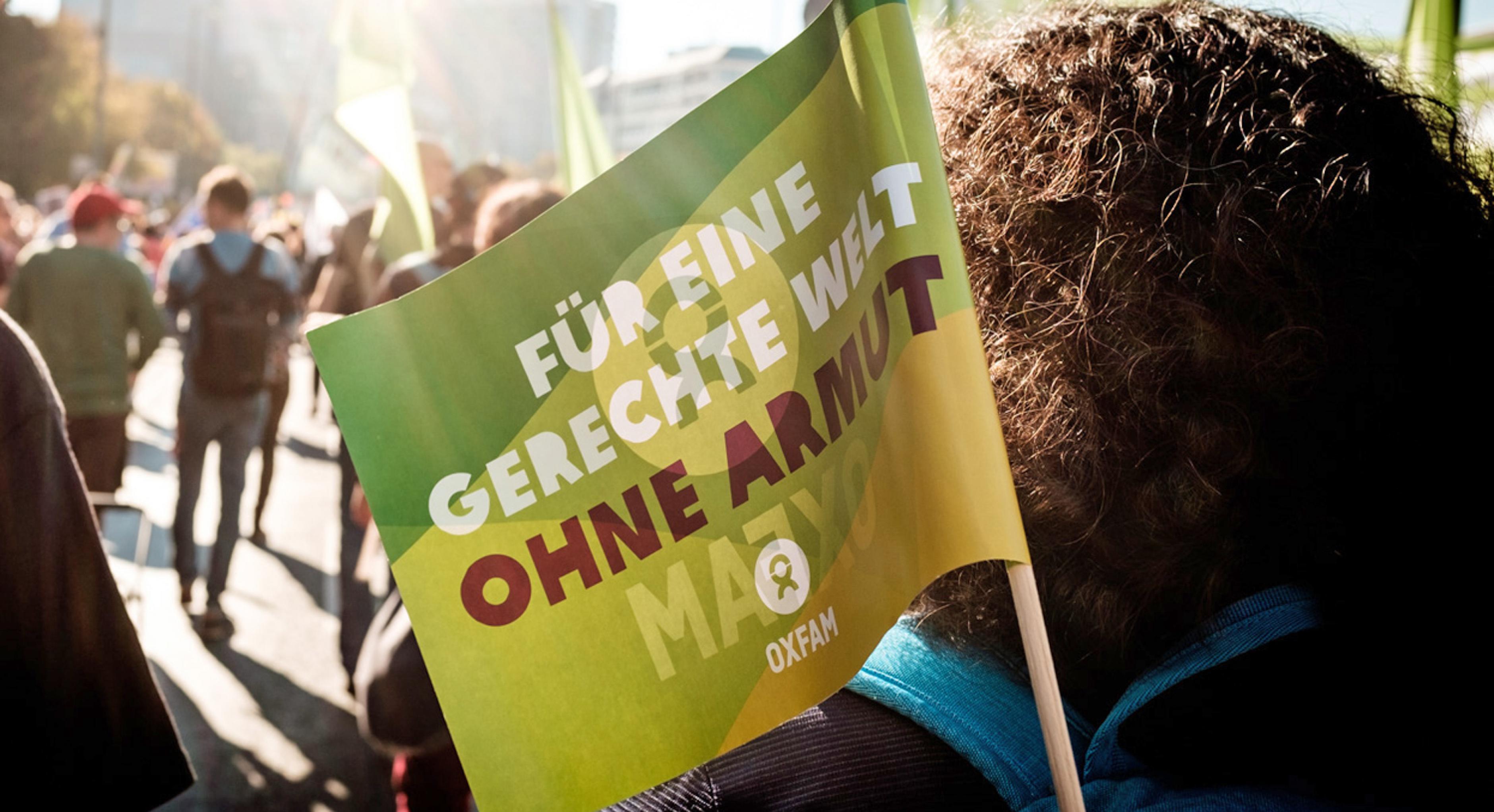 Eine Oxfam-Fahne ist auf einer Demonstration zu sehen