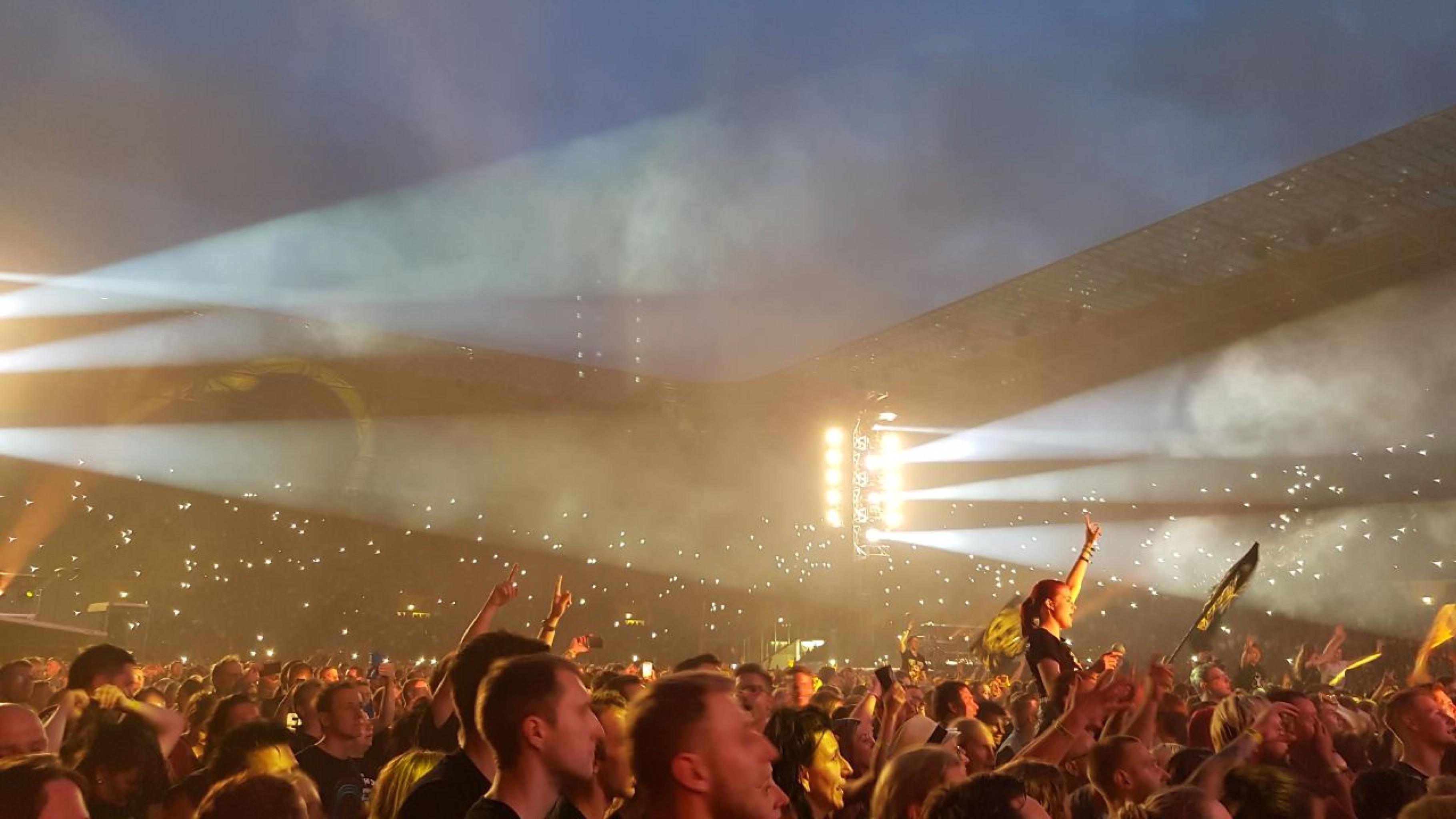Auf einem großen Konzert singt das Publikum und schwenkt Fahnen im vom Nebel reflektierten Scheinwerferlicht
