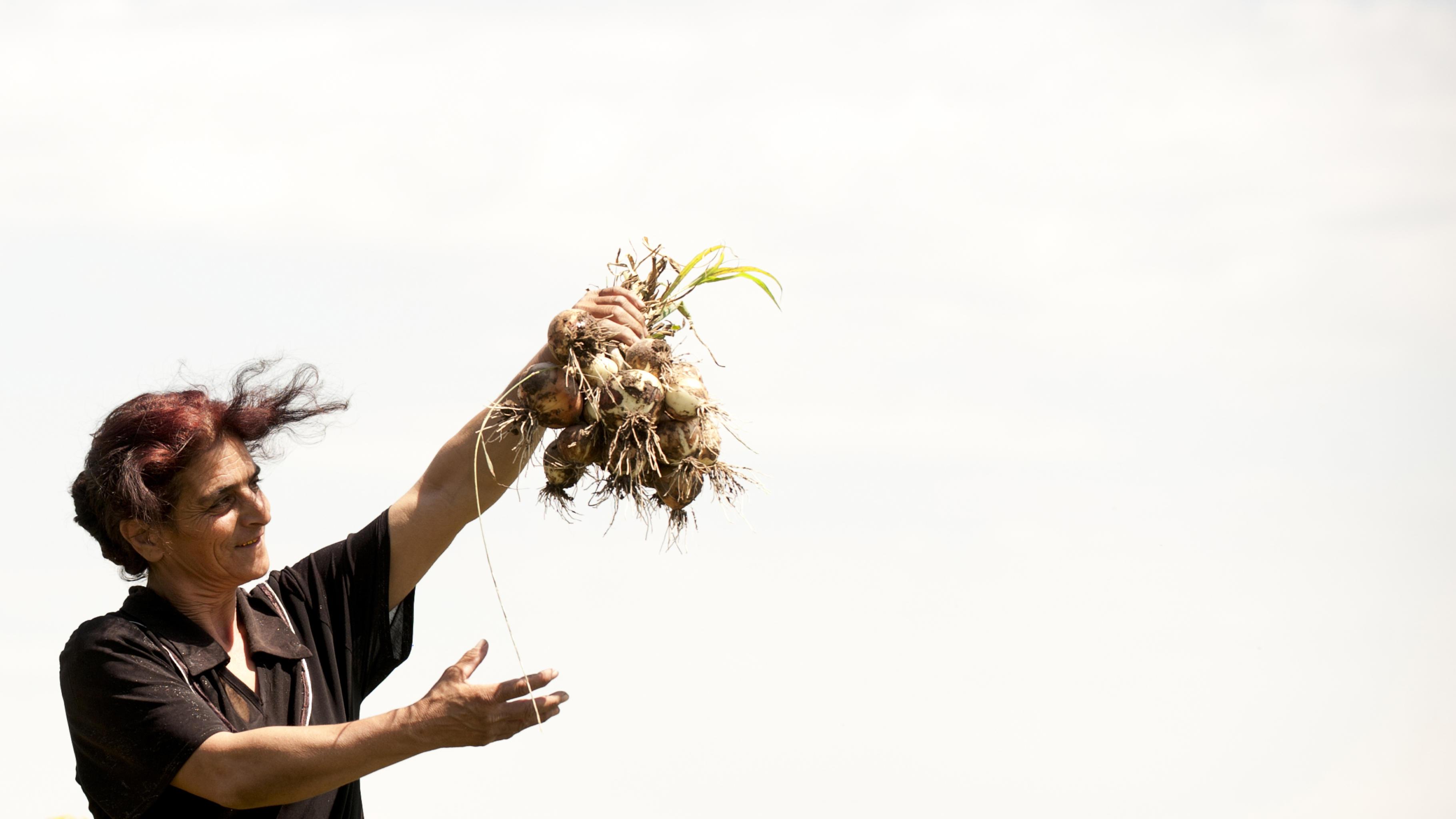 Eine Frau hält ein Bündel Zwiebeln in die Luft