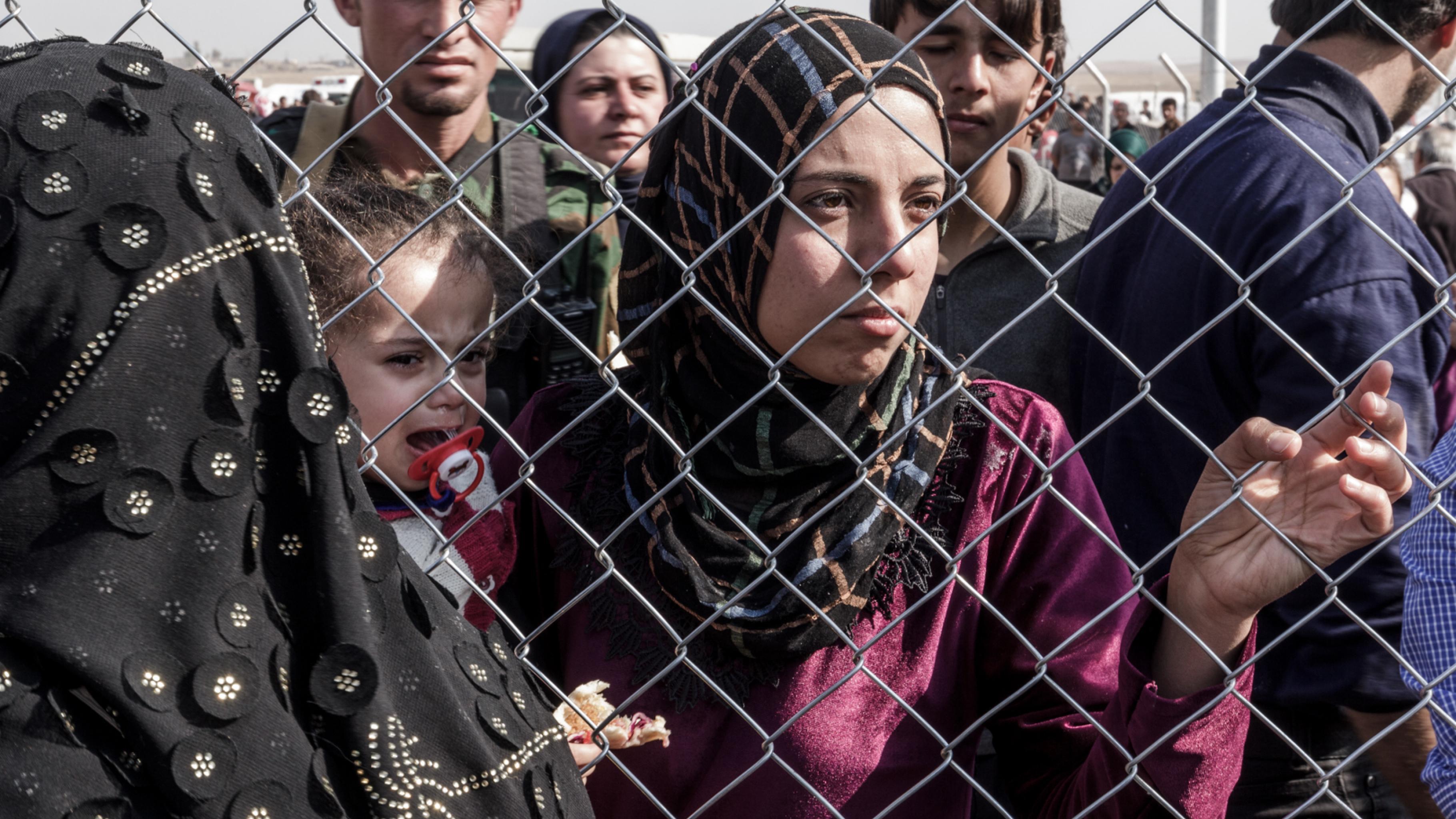 Frau mit Kind an einem Zaun