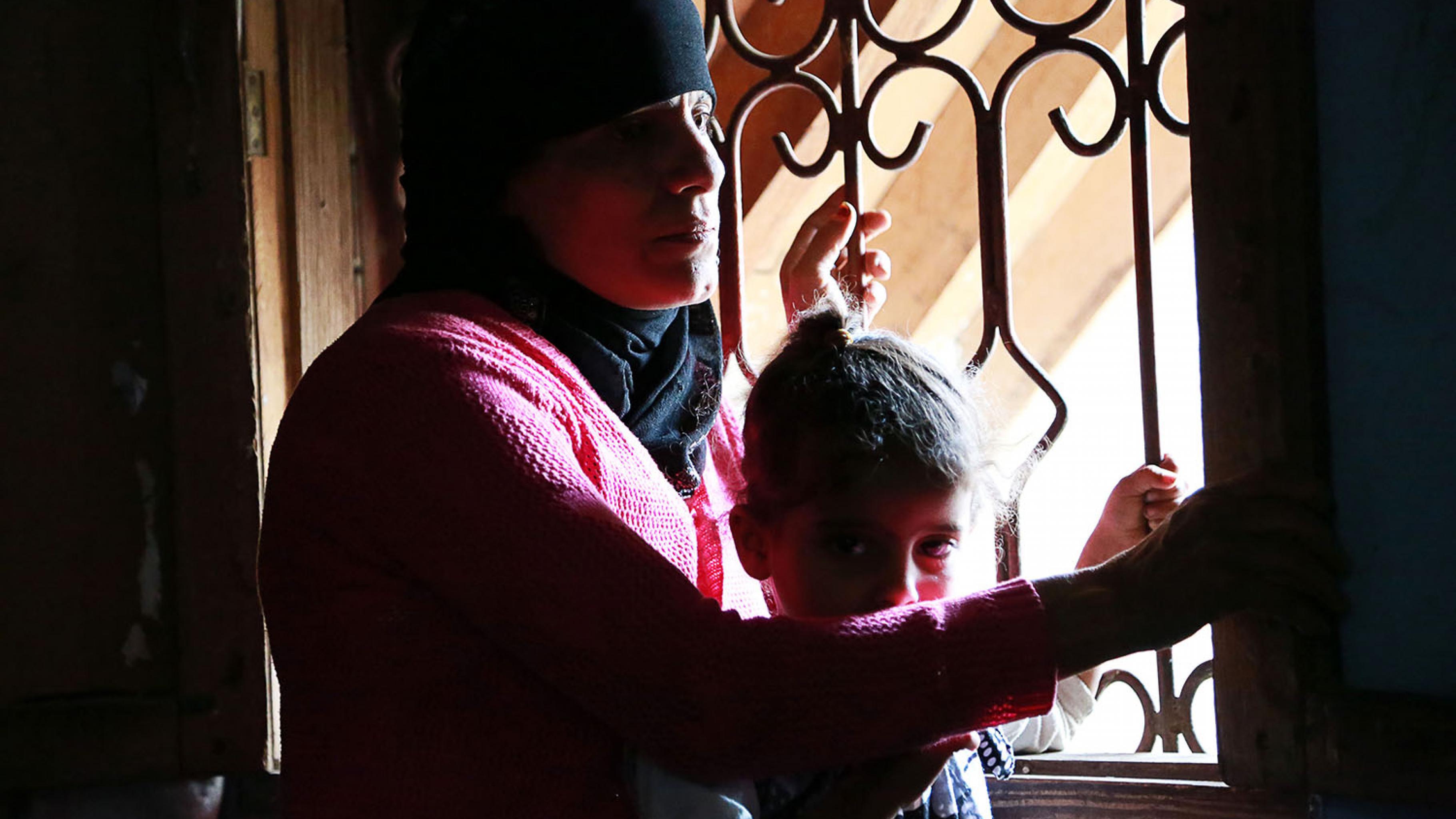 Om Nawal sitzt mit ihrem Enkelkind am Fenster