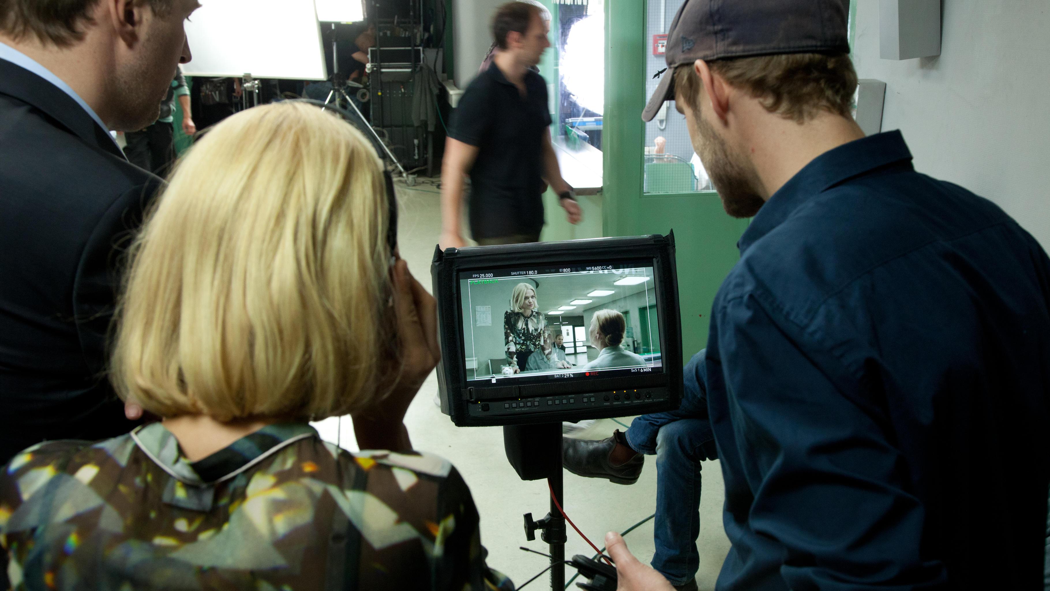 Die Darsteller schauen sich die gedrehten Szenen an