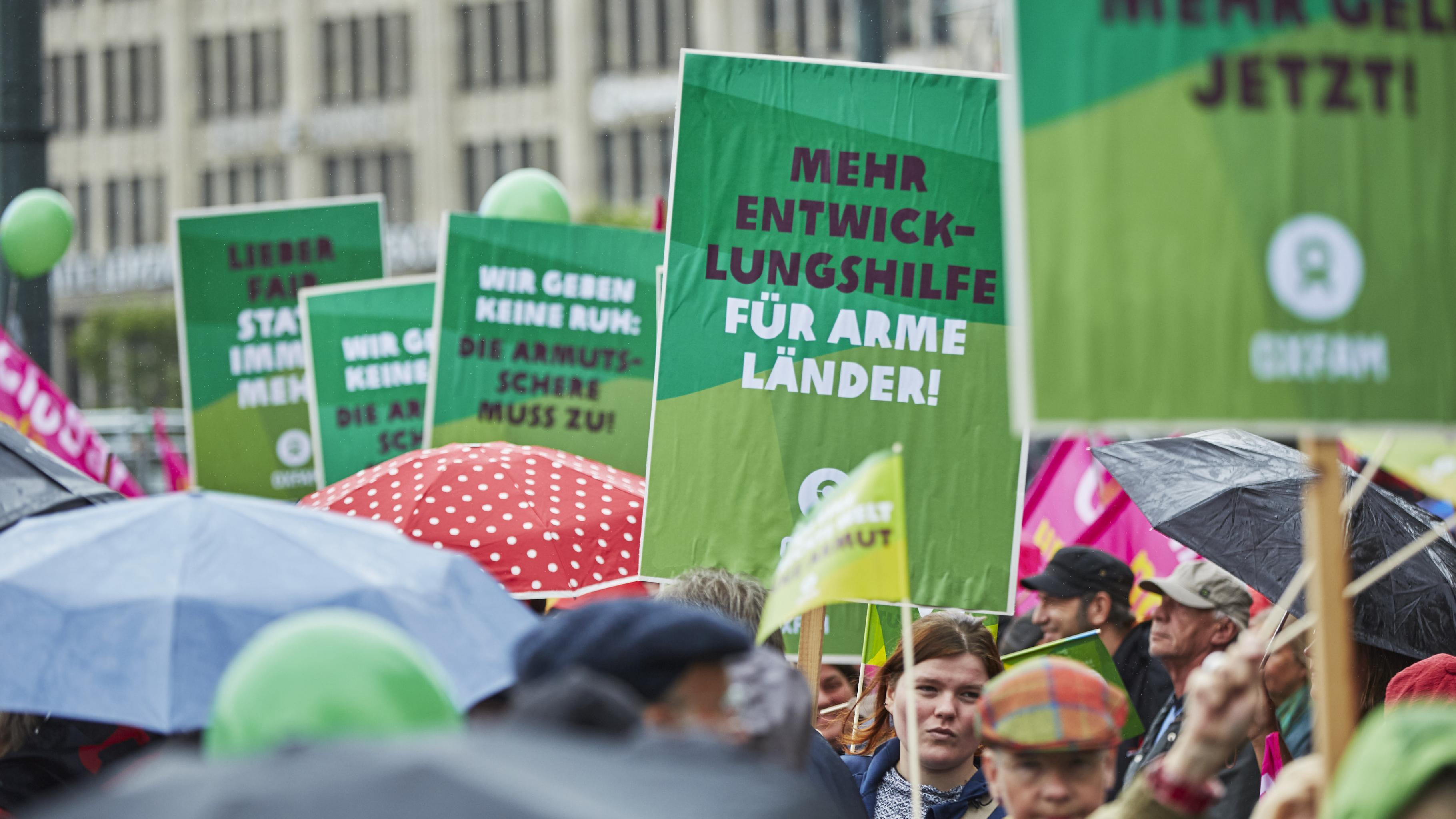 Bei einer G20 Protestdemonstration sind einige Plakate zu sehen, auf denen mehr Ausgaben für Entwicklungshilfe gefordert wird.