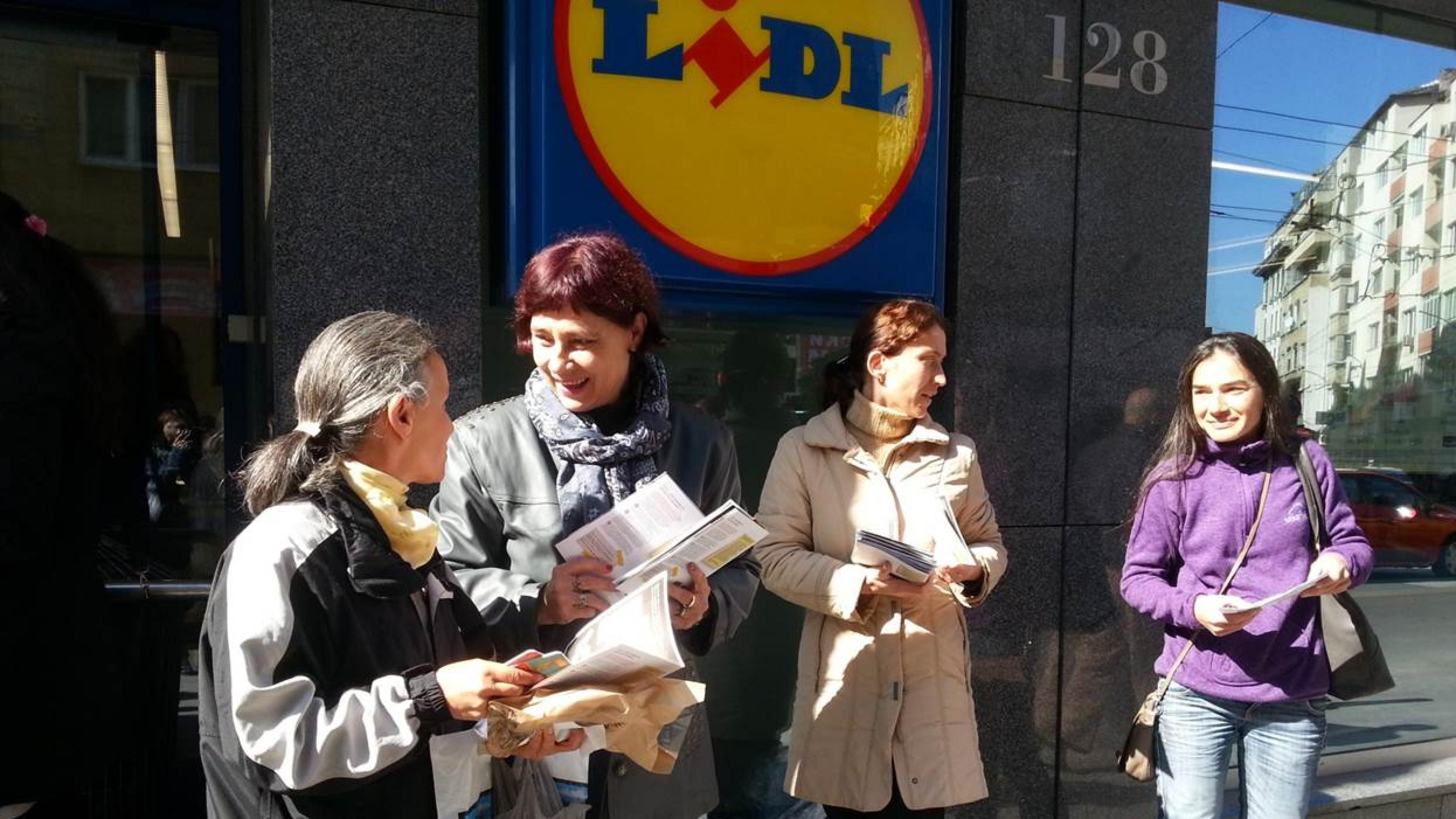 Frauen stehen vor einer Lidl-Filiale und verteilen Flugblätter an Passantinnen