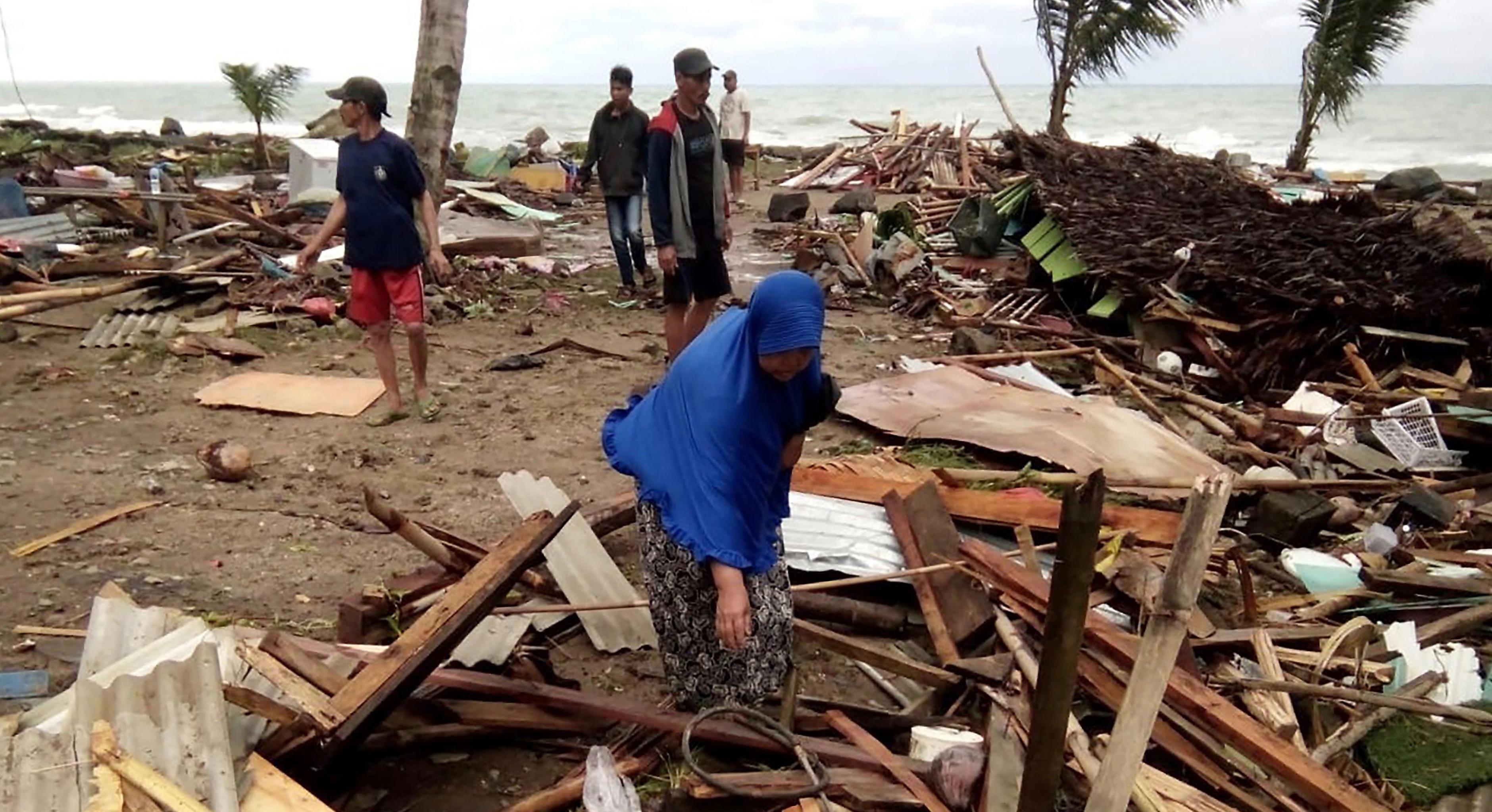 Bewohner inspizieren die Schäden an ihren Häusern am Strand von Carita, nachdem das Gebiet am 22. Dezember von einem Tsunami heimgesucht wurde.