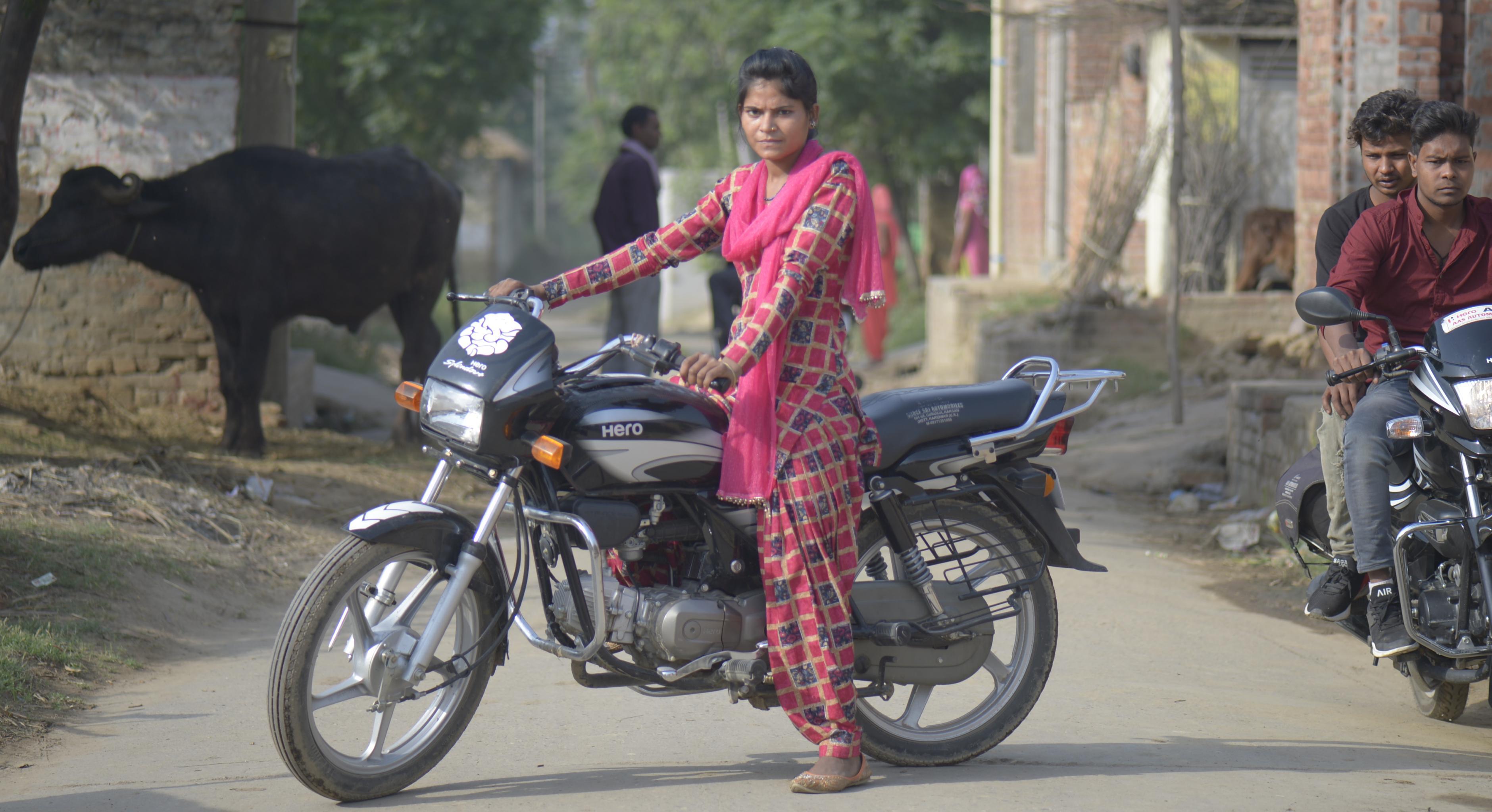 Eine junge indische Frau sitzt auf einem Motorrad; neben ihr zwei Männer auf einem anderen Motorrad