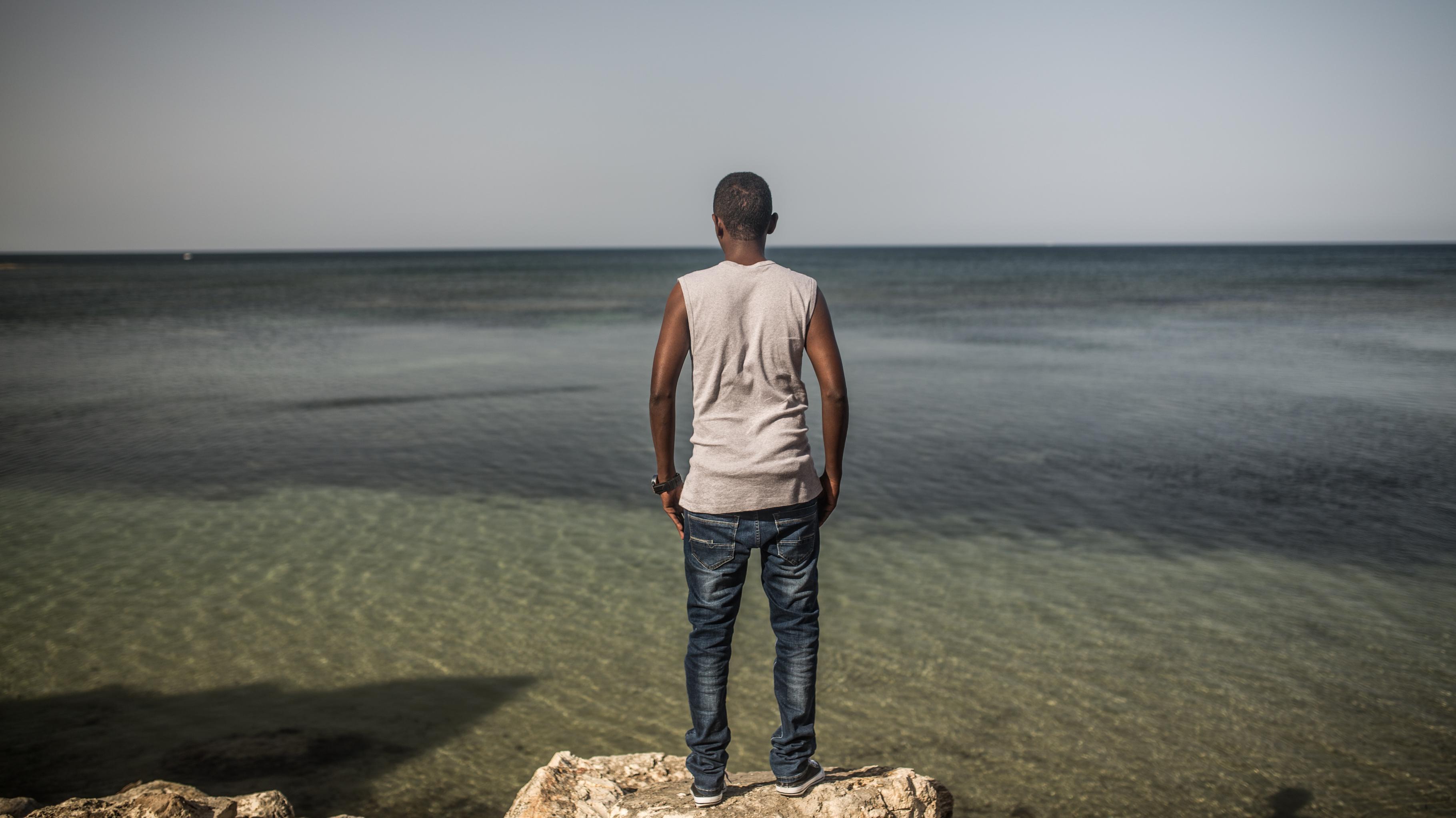 Ein Mann steht auf einem Felsen und blickt aufs Meer.