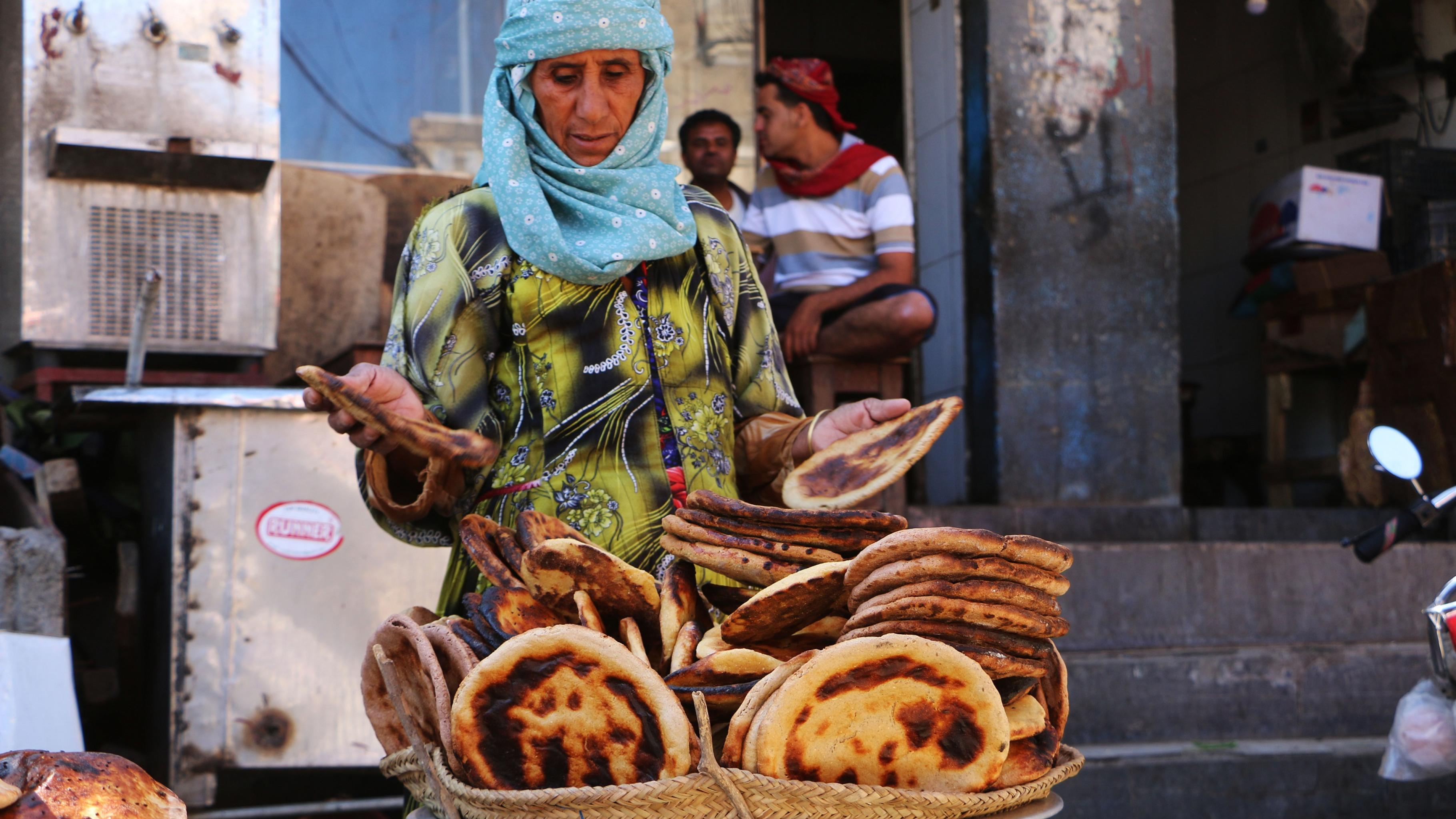 Eine Frau verkauft Fladenbrot aus einem großen Korb.